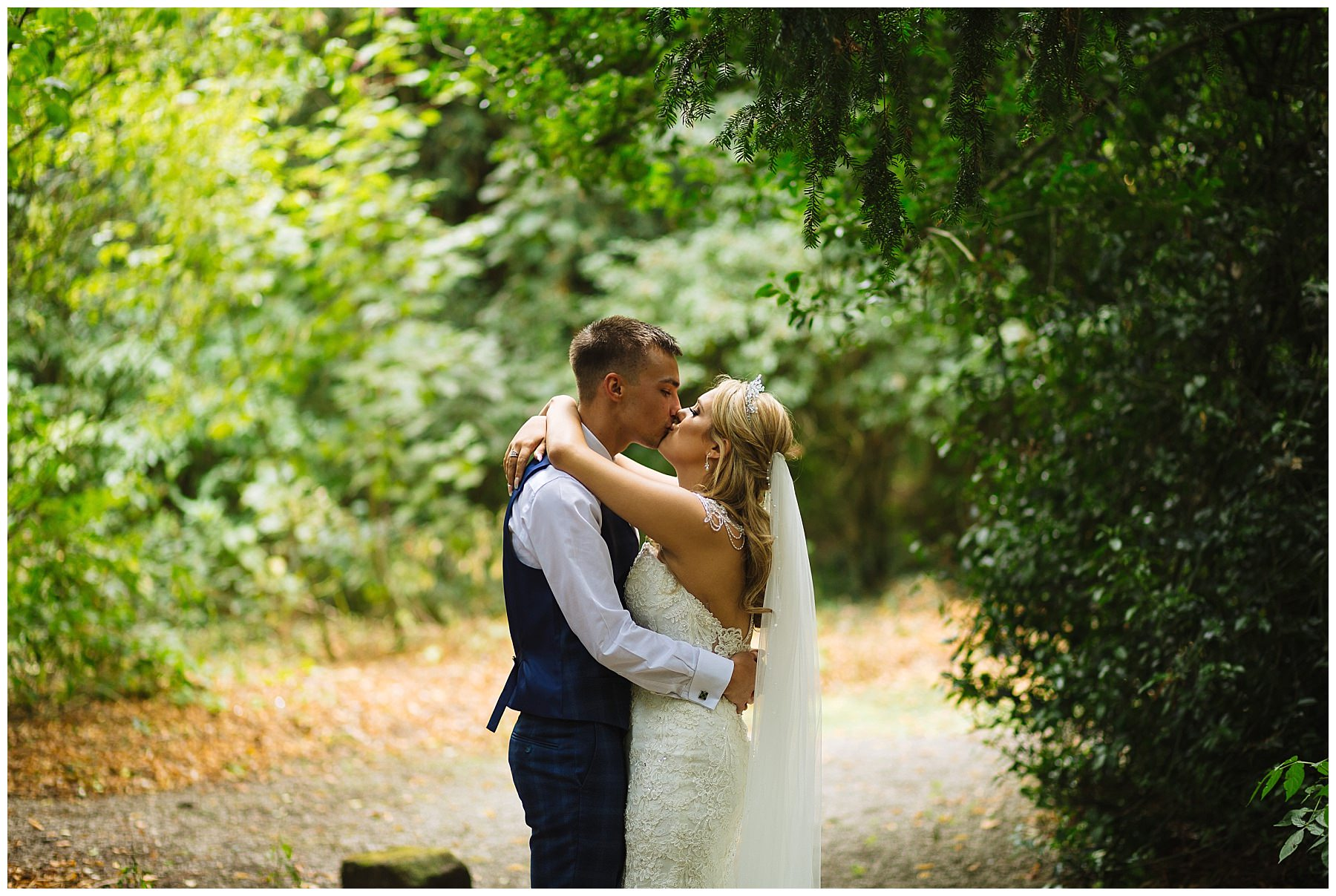 married couple kiss under trees at Bartle Hall