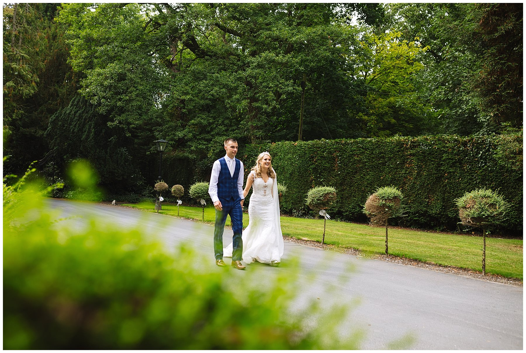 Wedding couple stroll through the gardens at bartle hall