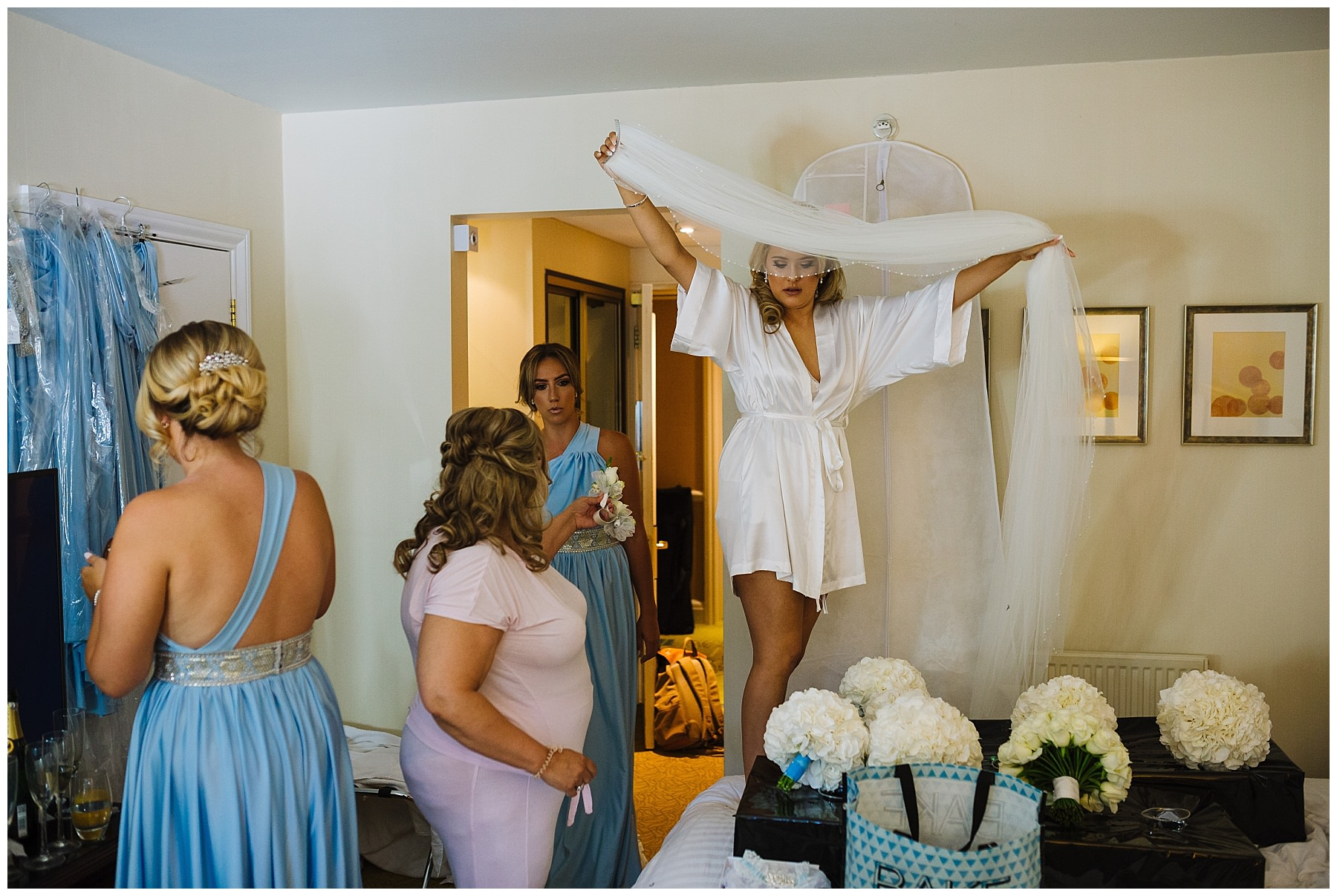 bride carries veil over beds at bridal prep