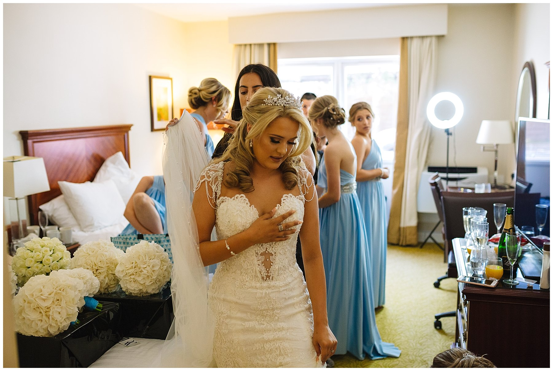 bride in wedding dress has finishing touches applied