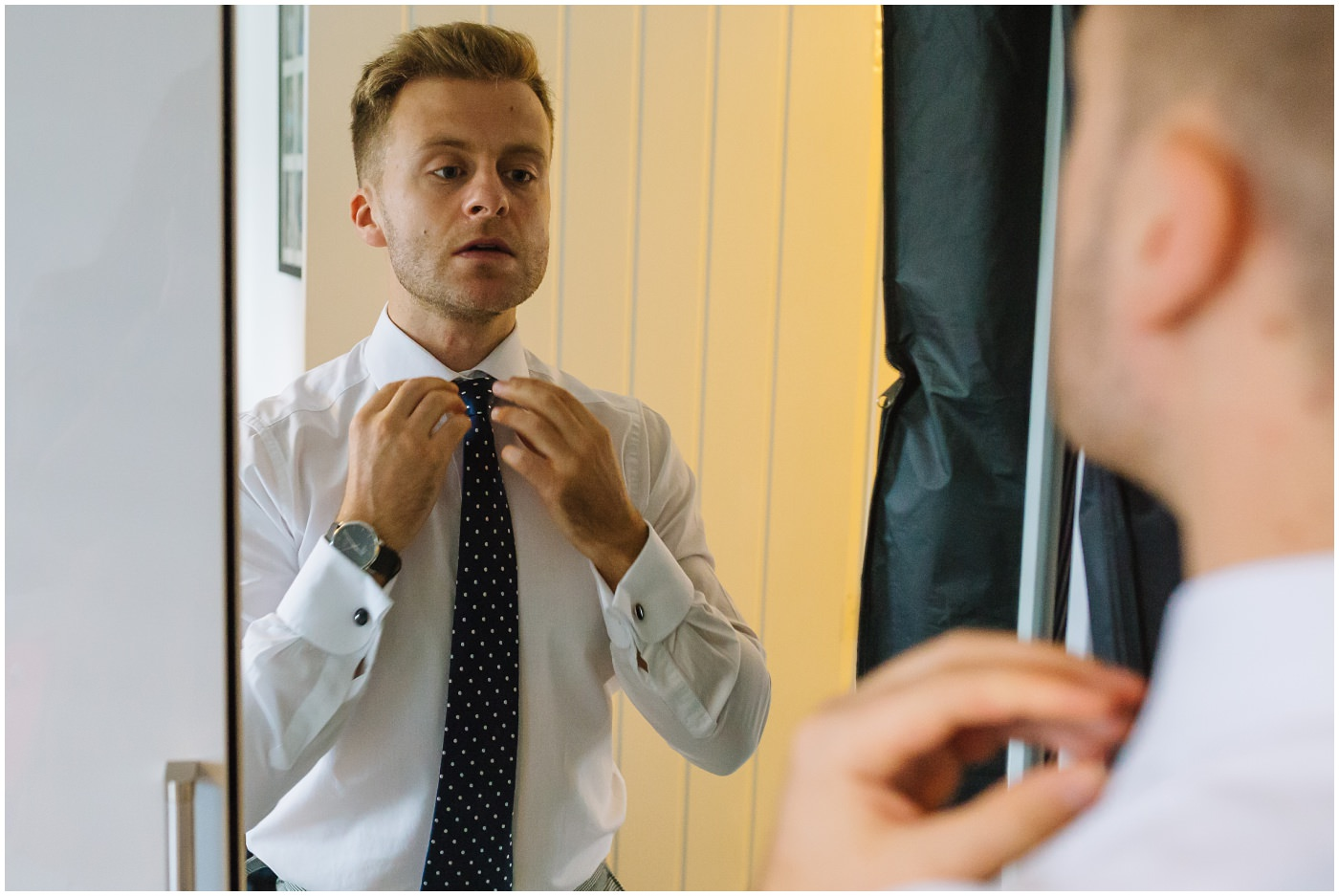 groom straightens tie in mirror