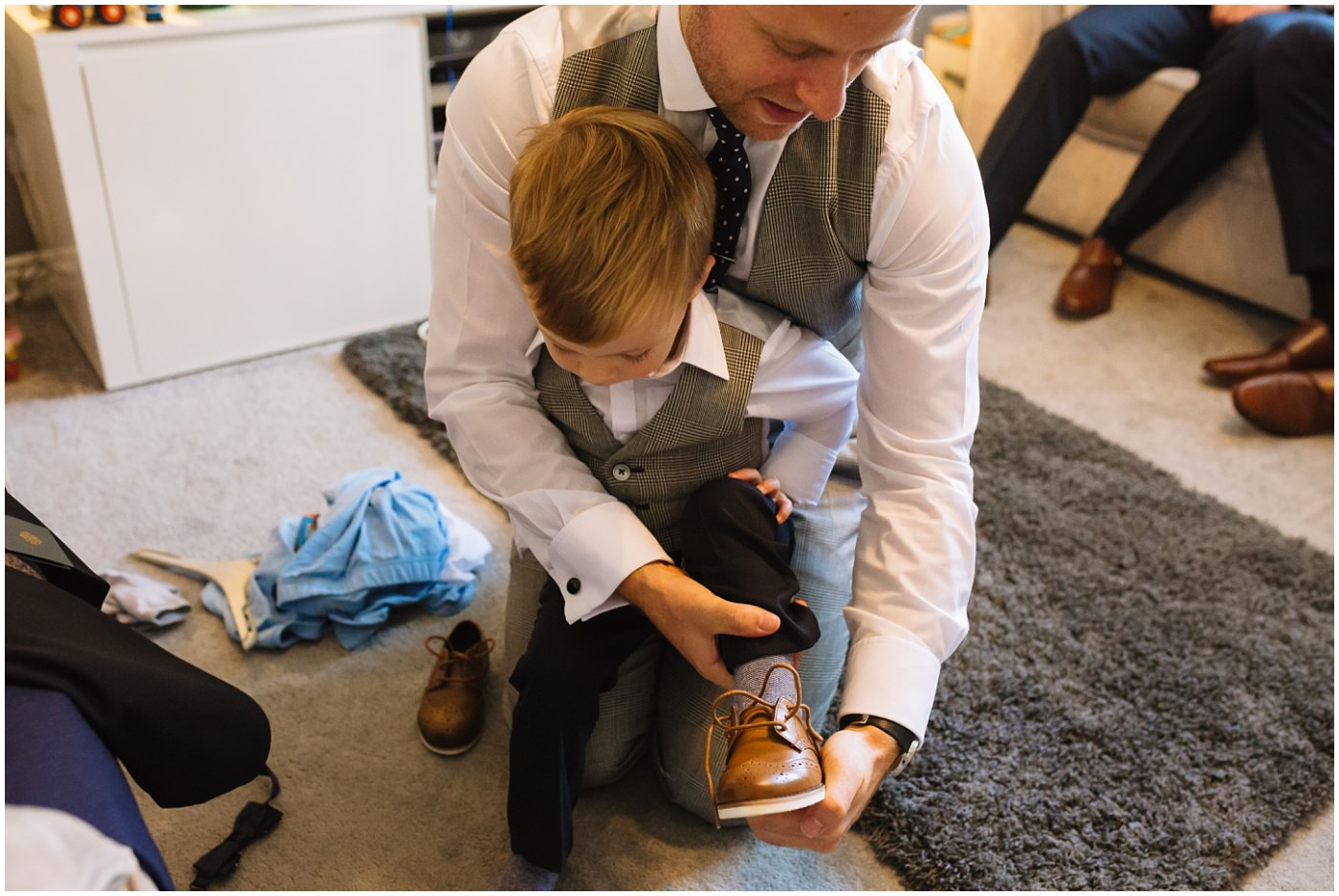 groom helps son with shoes
