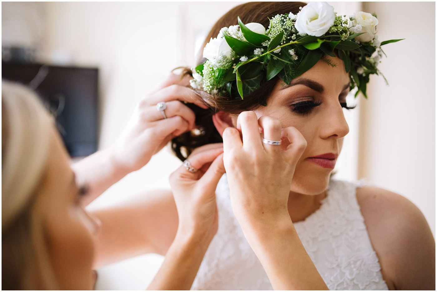 bridesmaid helps bride with ear rings