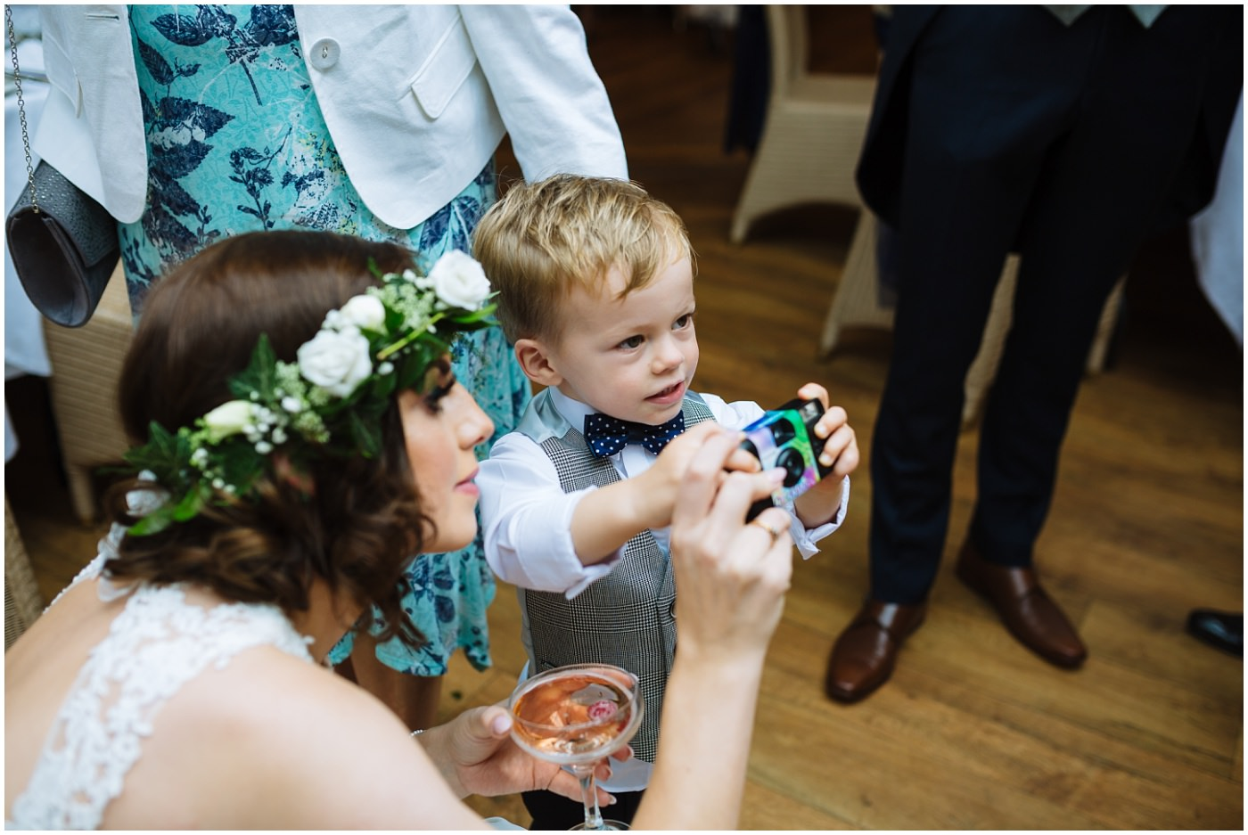 bride and son play with disposable camera