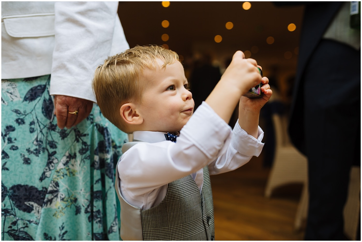 little boy plays with disposable camera at a wedding