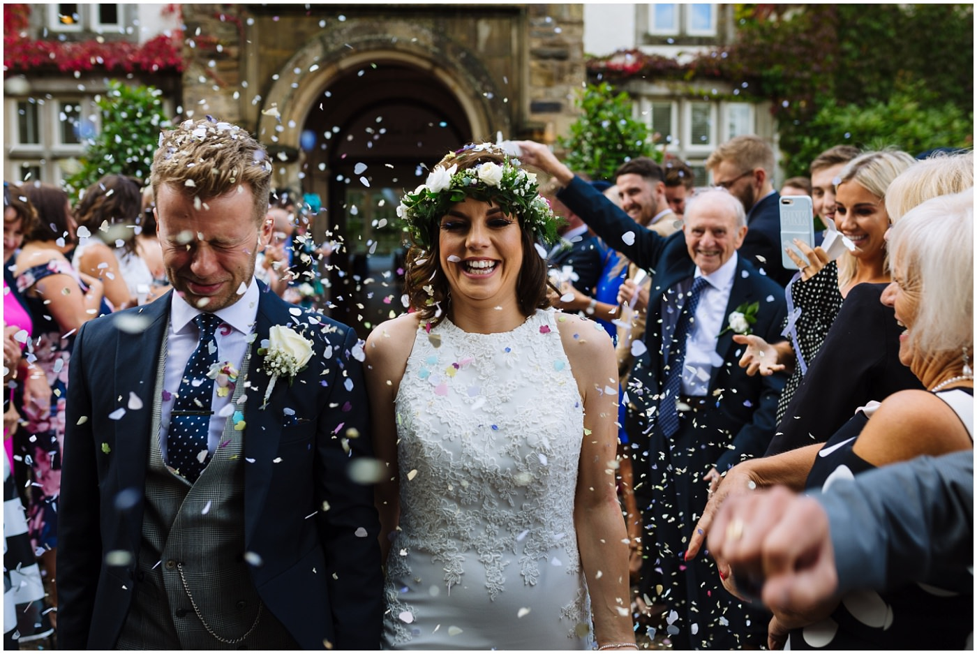 Bride and Groom walk through shower of confetti at mitton hall
