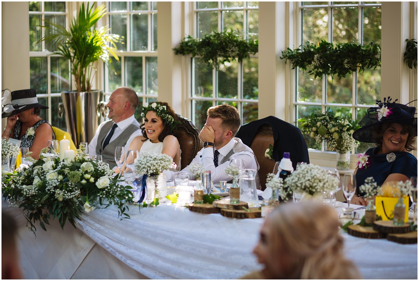 groom hides his face in reaction to best mans speech