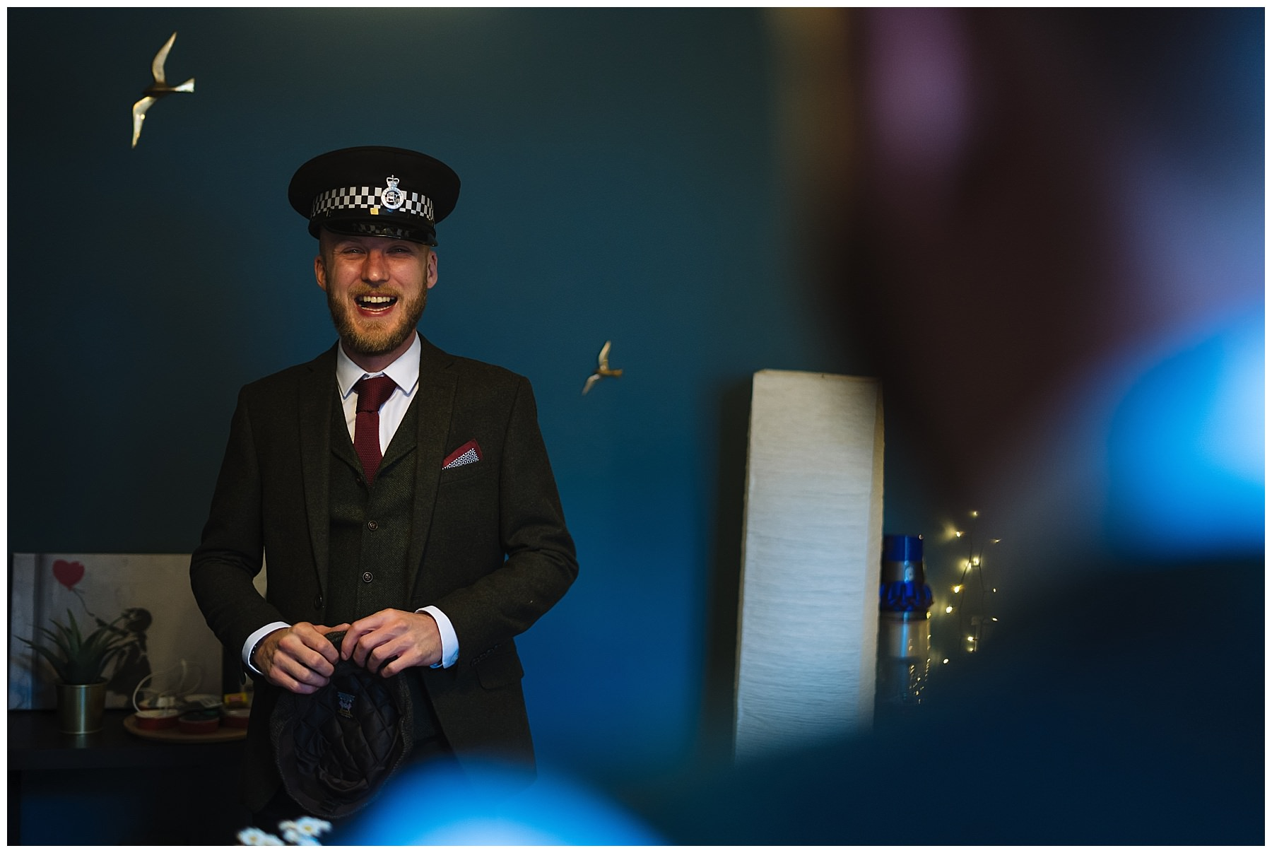 groom laughing wearing police hat