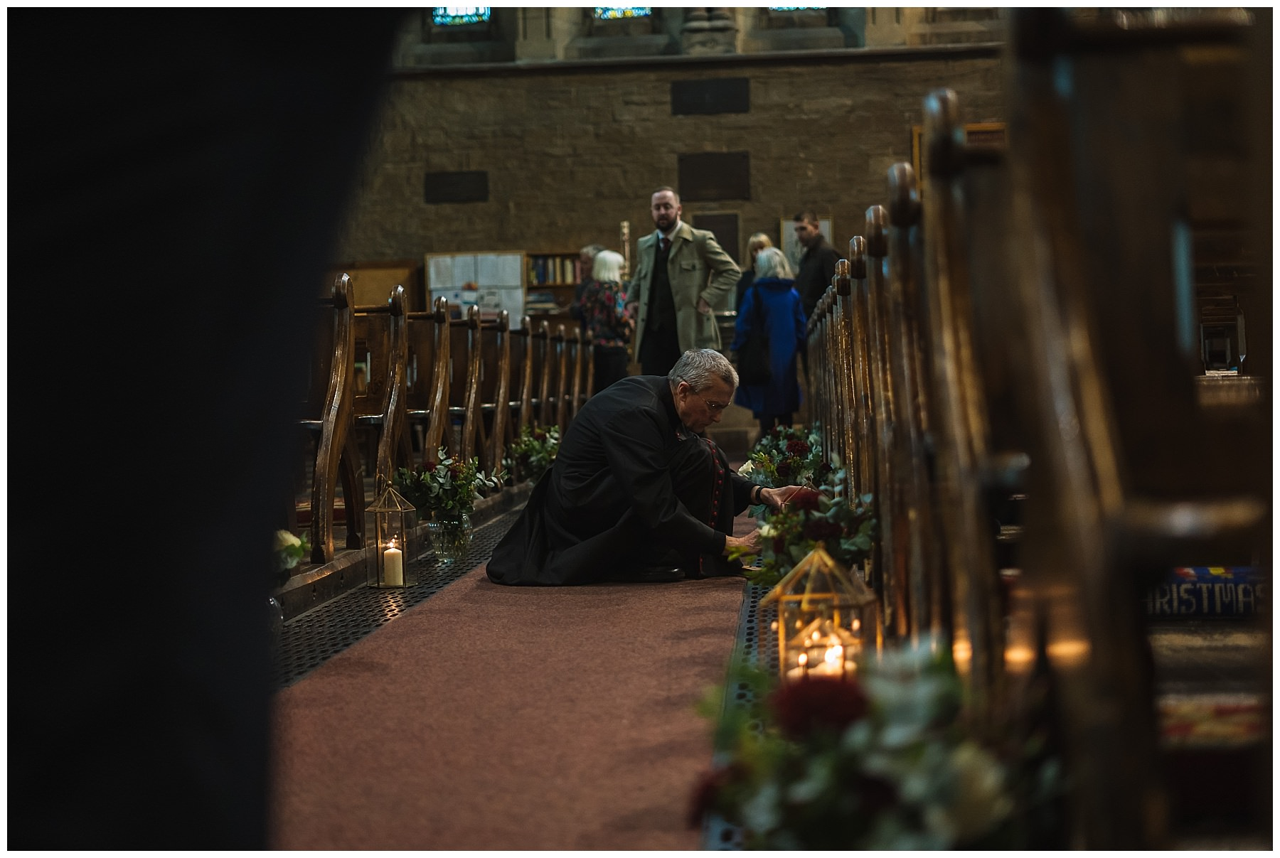 priest lighting candles in church