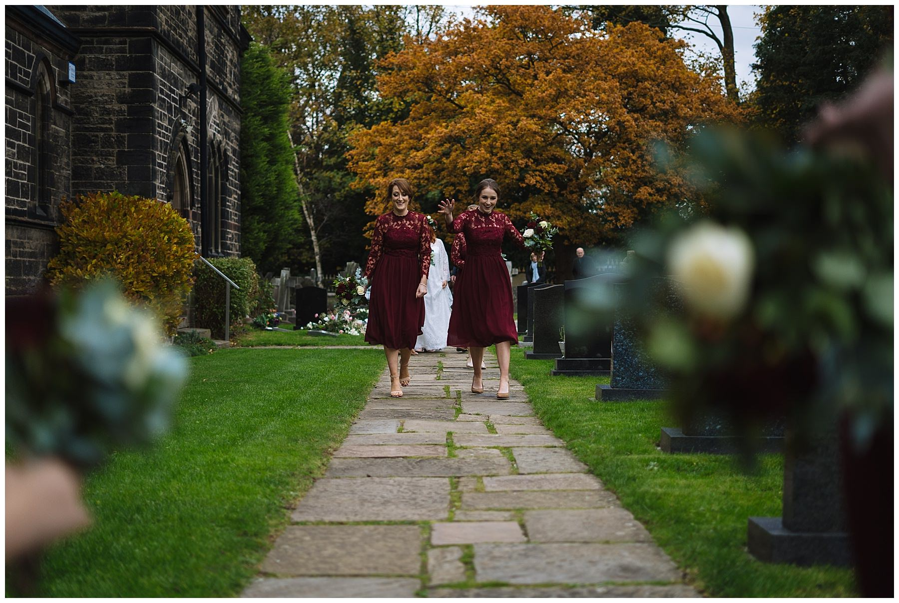 bridesmaids walk towards church in burgundy dresses