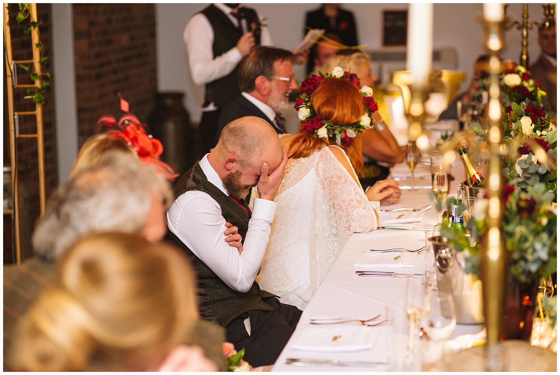 Groom hies head in hands during best mans speech