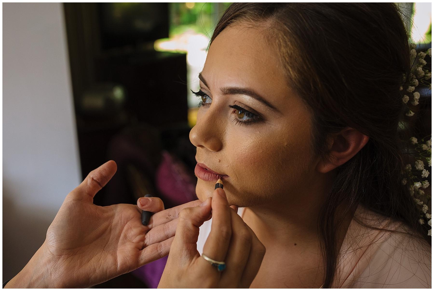 make up artist applies bridal lip liner