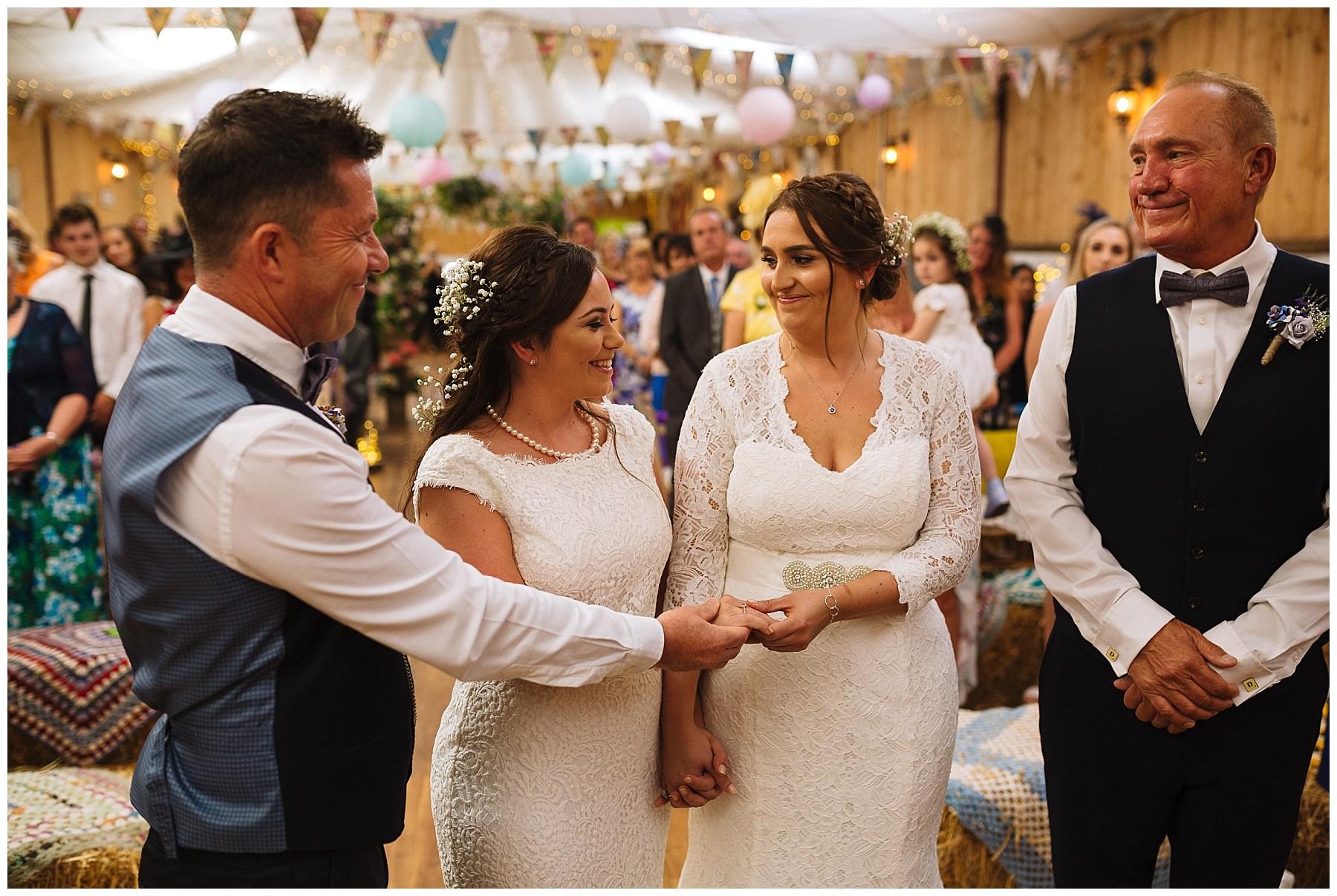 proud fathers exchange brides hands during wedding ceremony