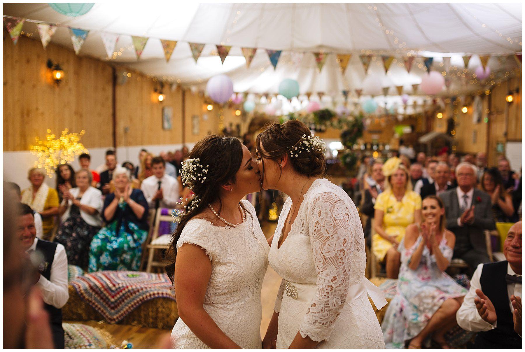 brides kiss during same sex wedding service
