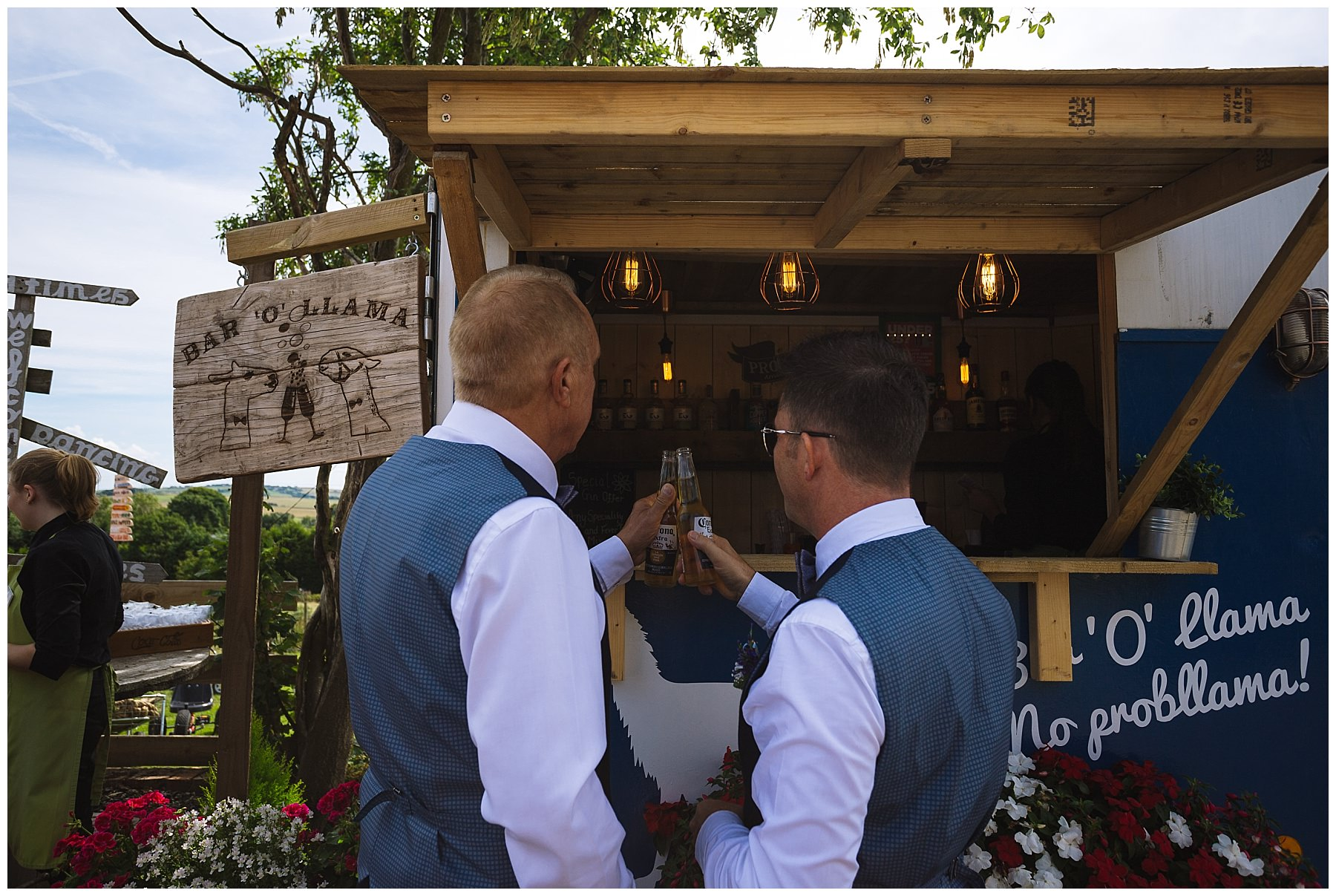 two dads share a beer after wedding ceremony