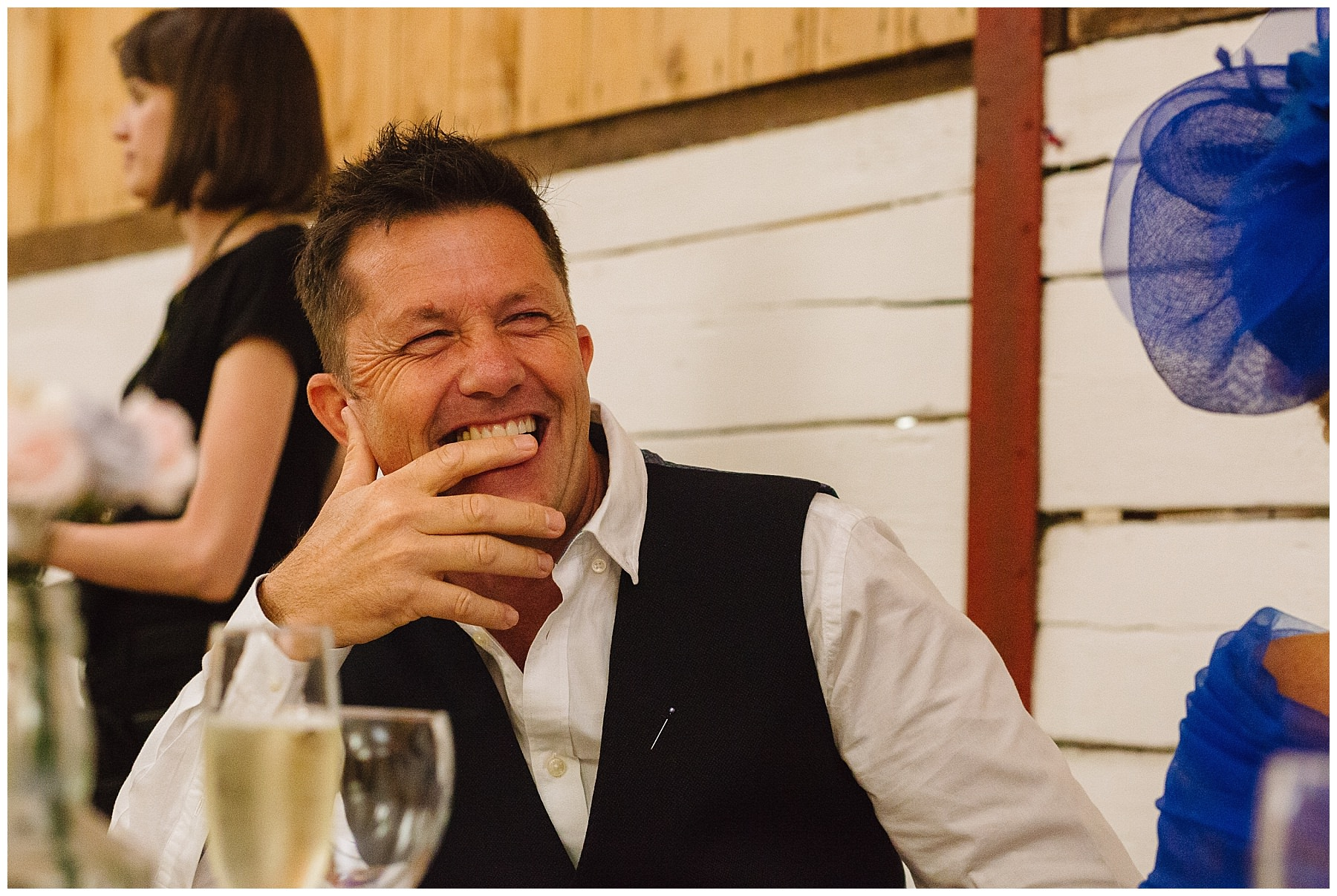 father of the bride laughs during speeches
