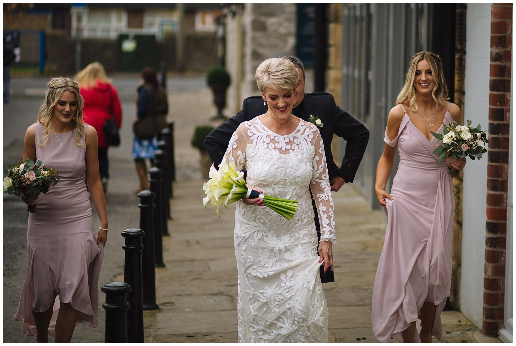 Bride and bridesmaids walk through holmes mill
