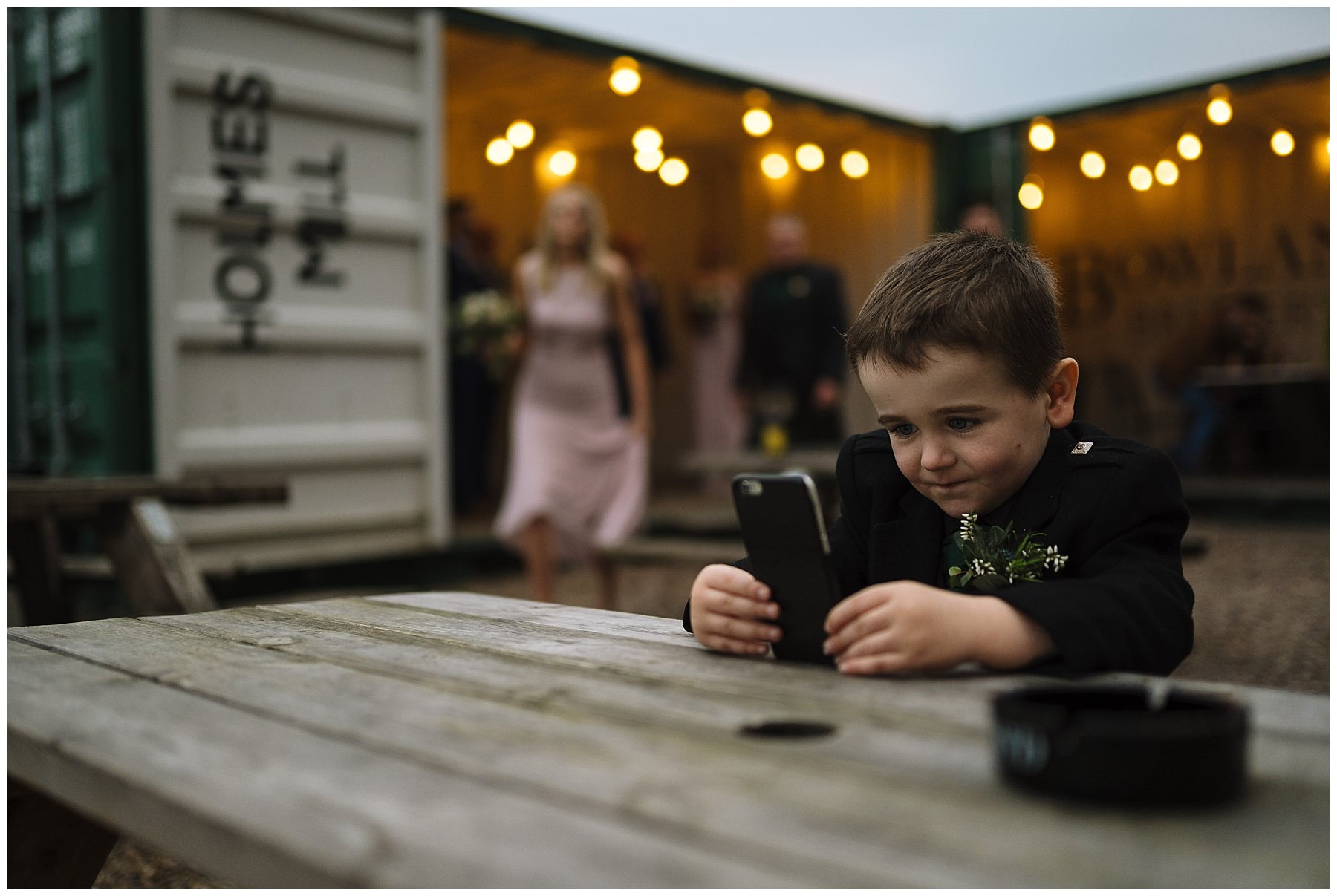 Page boy playing on phone during wedding