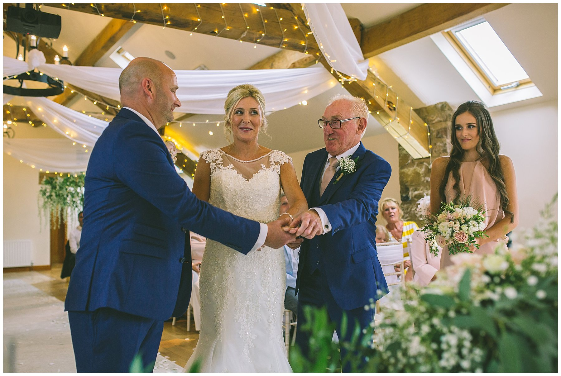 father of the bride passes daughters hand to her husband