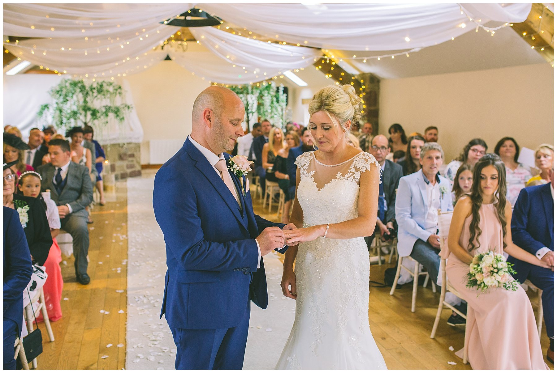bride and groom exchange wedding rings during beeston manor wedding ceremony