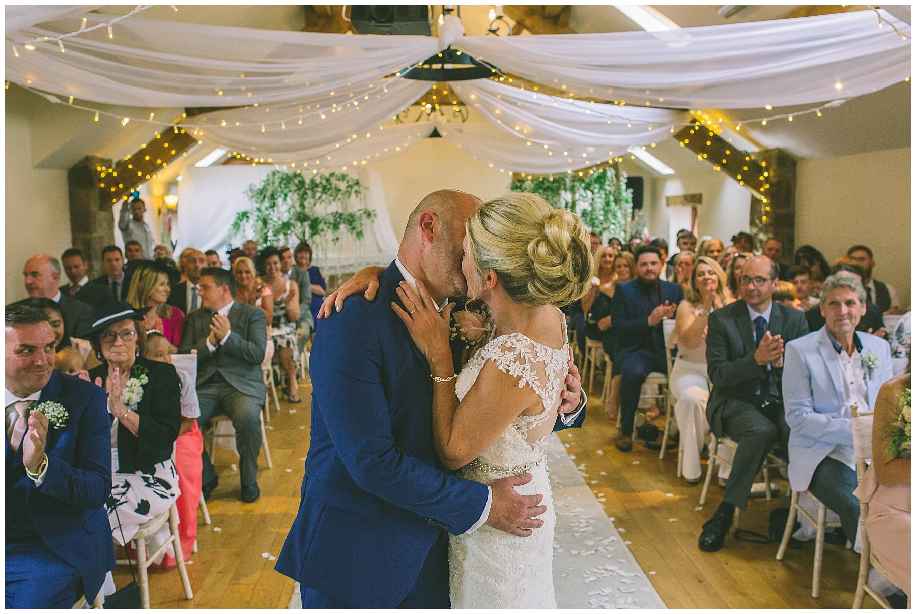 bride and grooms first kiss in beeston manor ceremony room