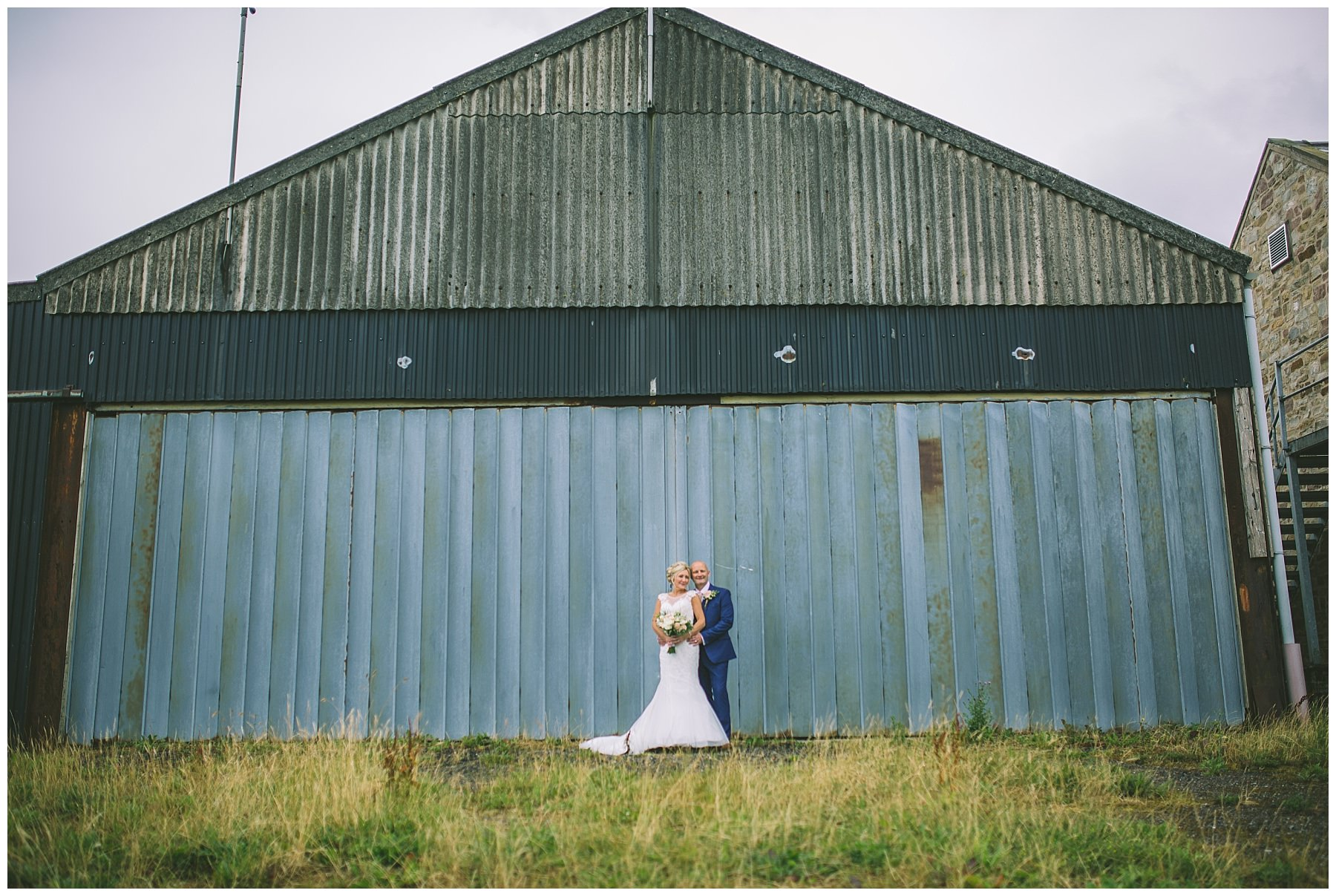 bride and groom stand in front of the iconic hanger at beeston manor