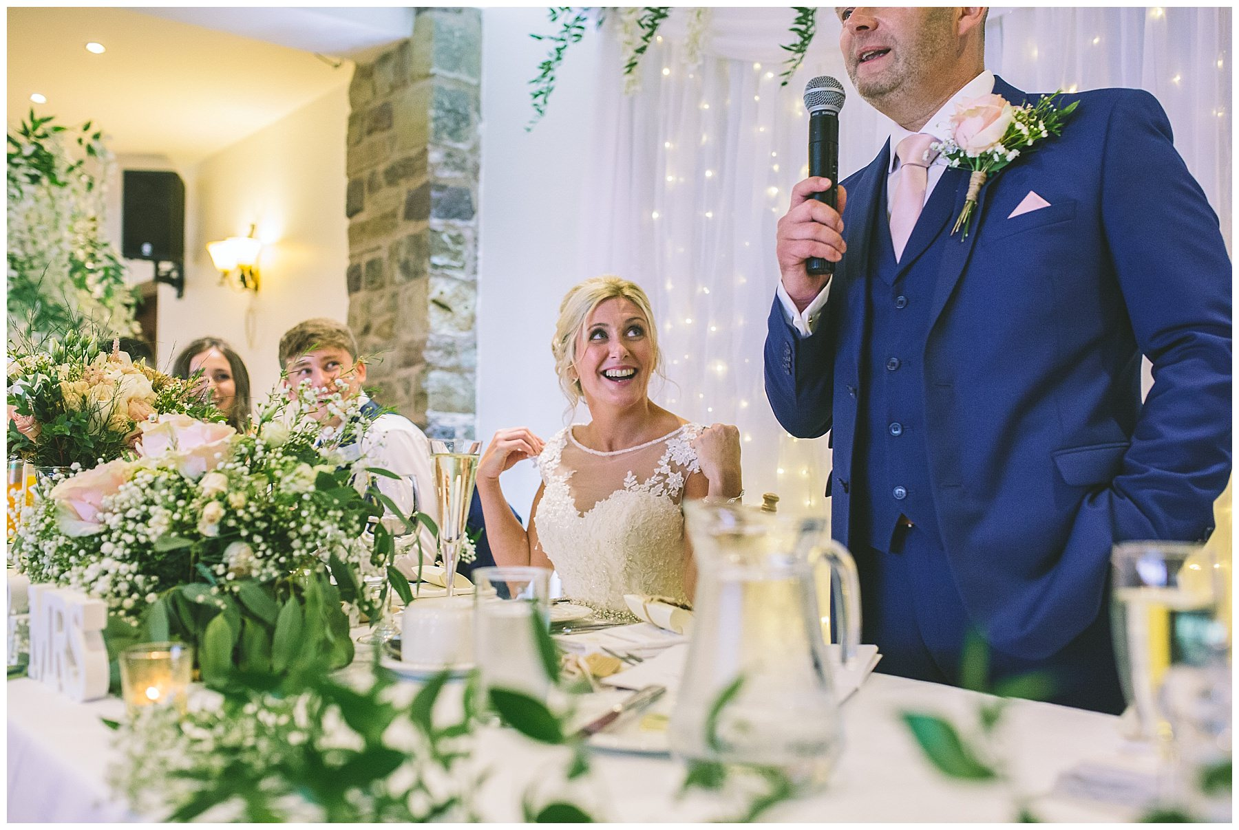 bride watches on as her husband address' wedding guests