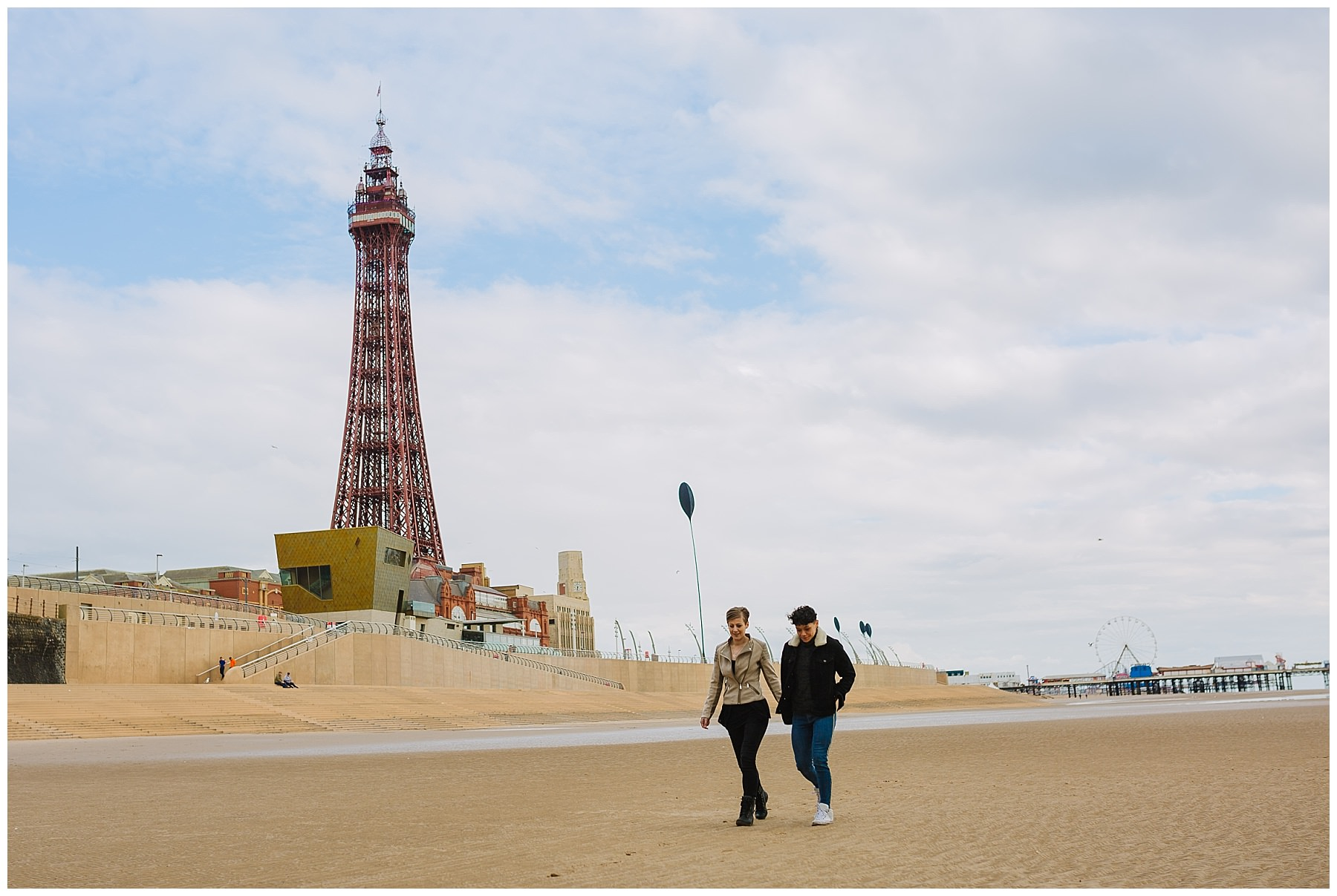 Same sex couple walk along blackpool beach