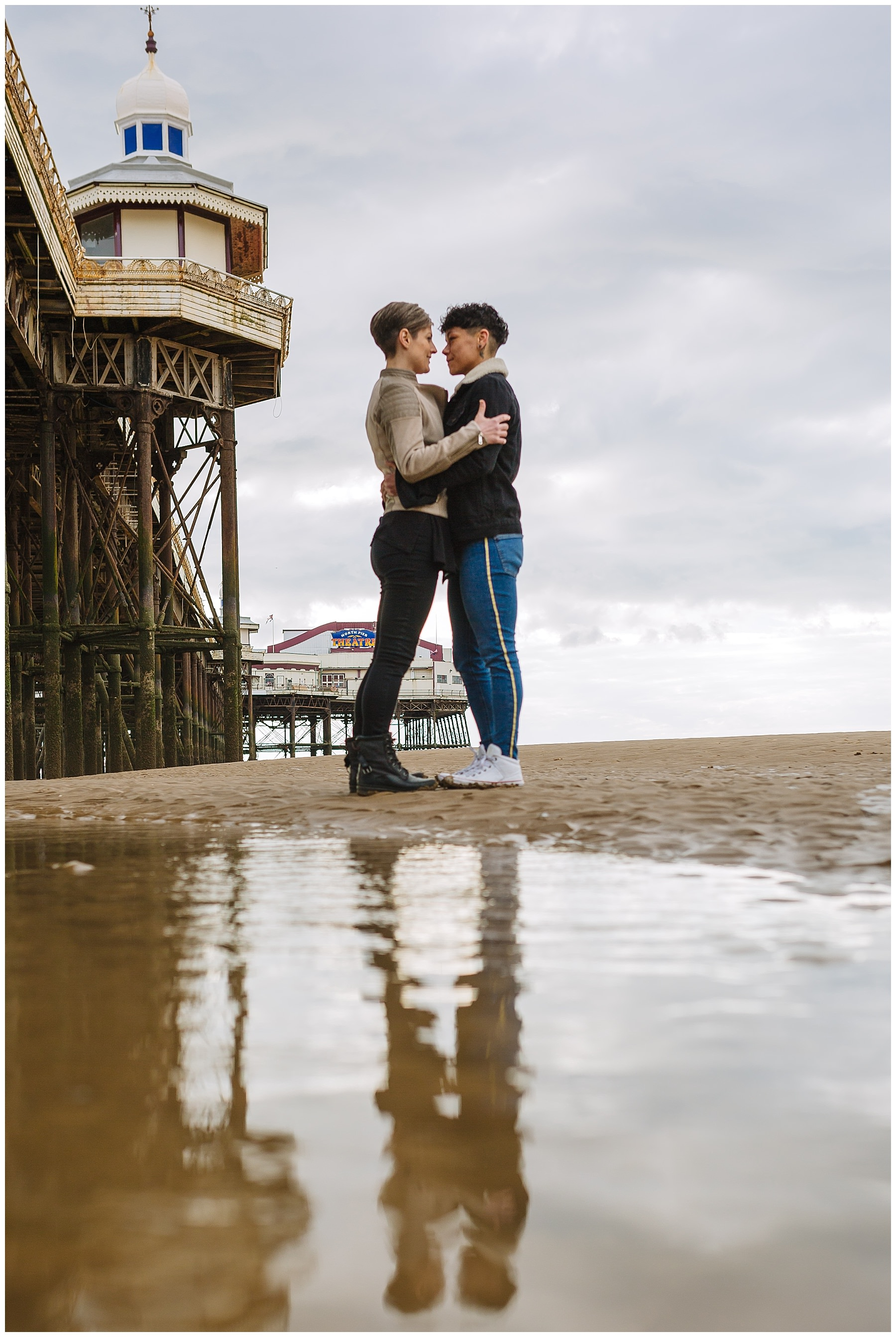 Couple reflected in standing water on Blackpool Beach