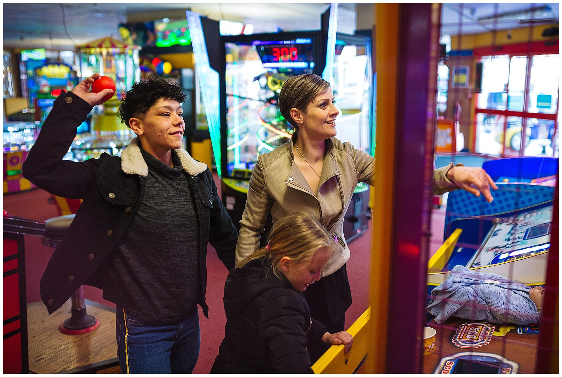 Couple and daughter enjoy arcades on the pier