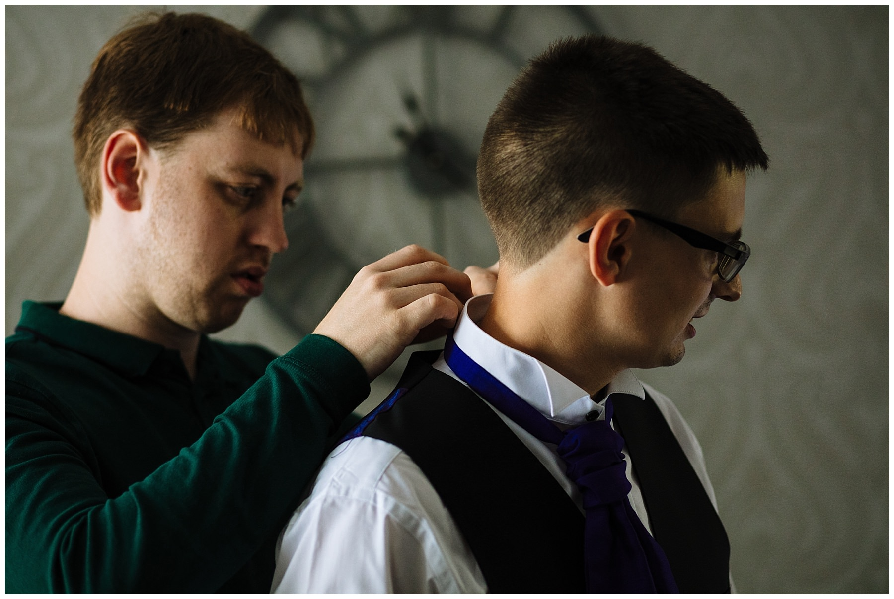 groomsman helps groom with his cravat