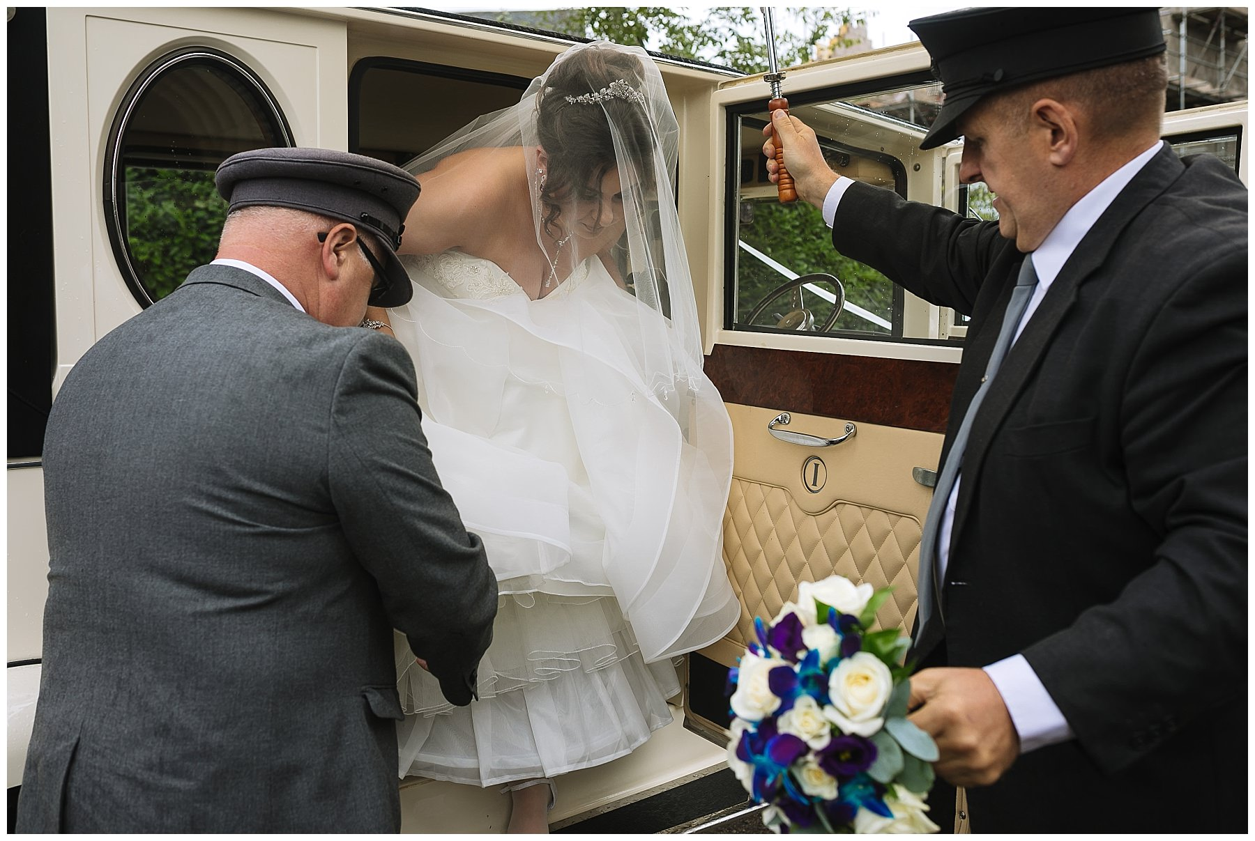 bride arrives at church in classic wedding car