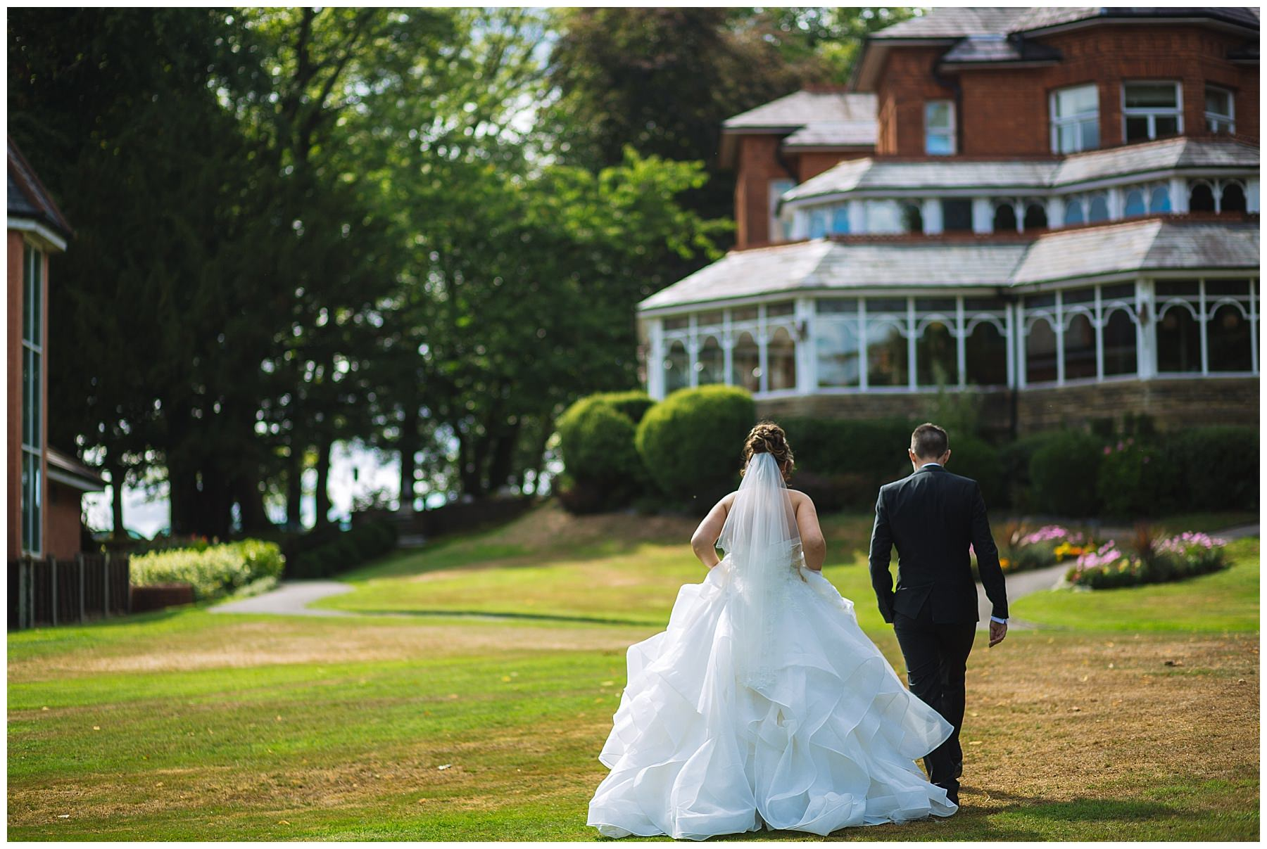 Married couple walk through the grounds of Kilhey Court