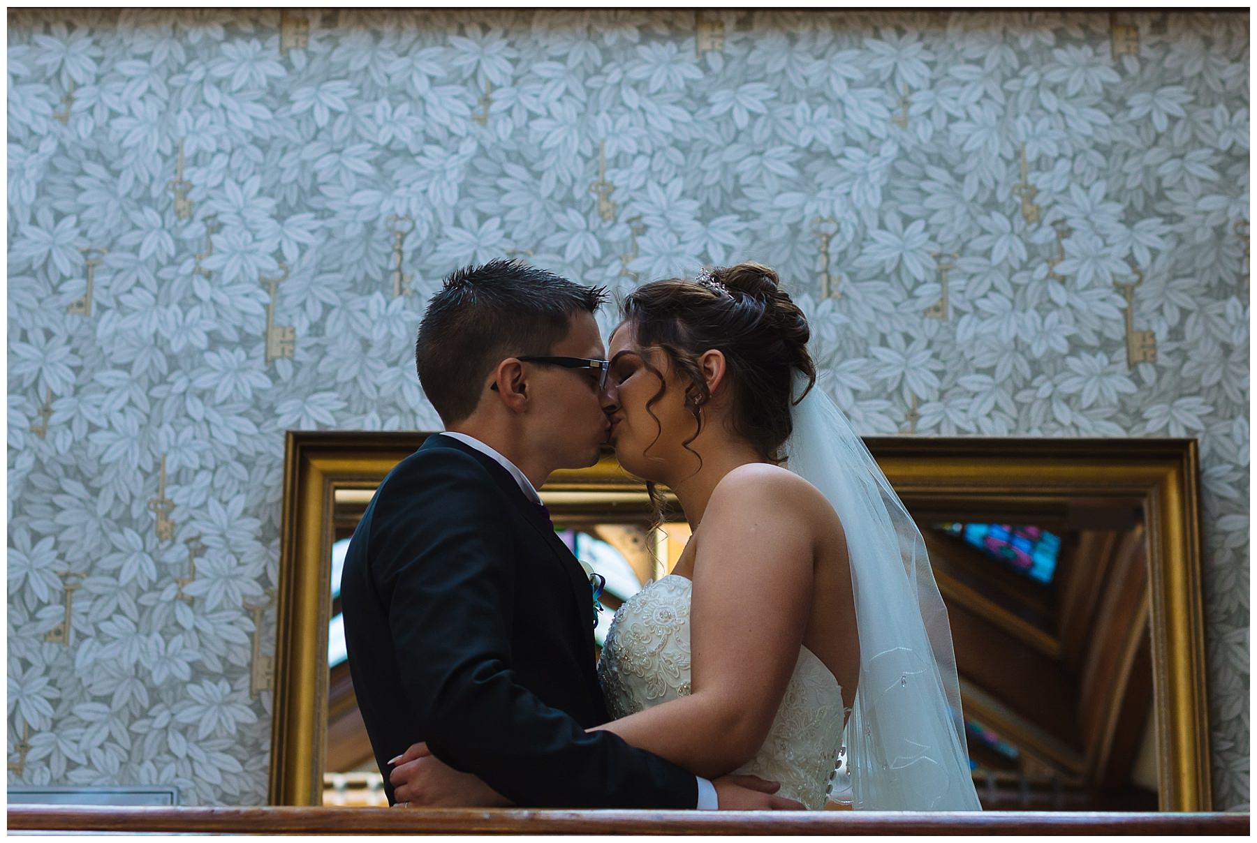 newly wed couple kiss on the stairs at Kilhey Court