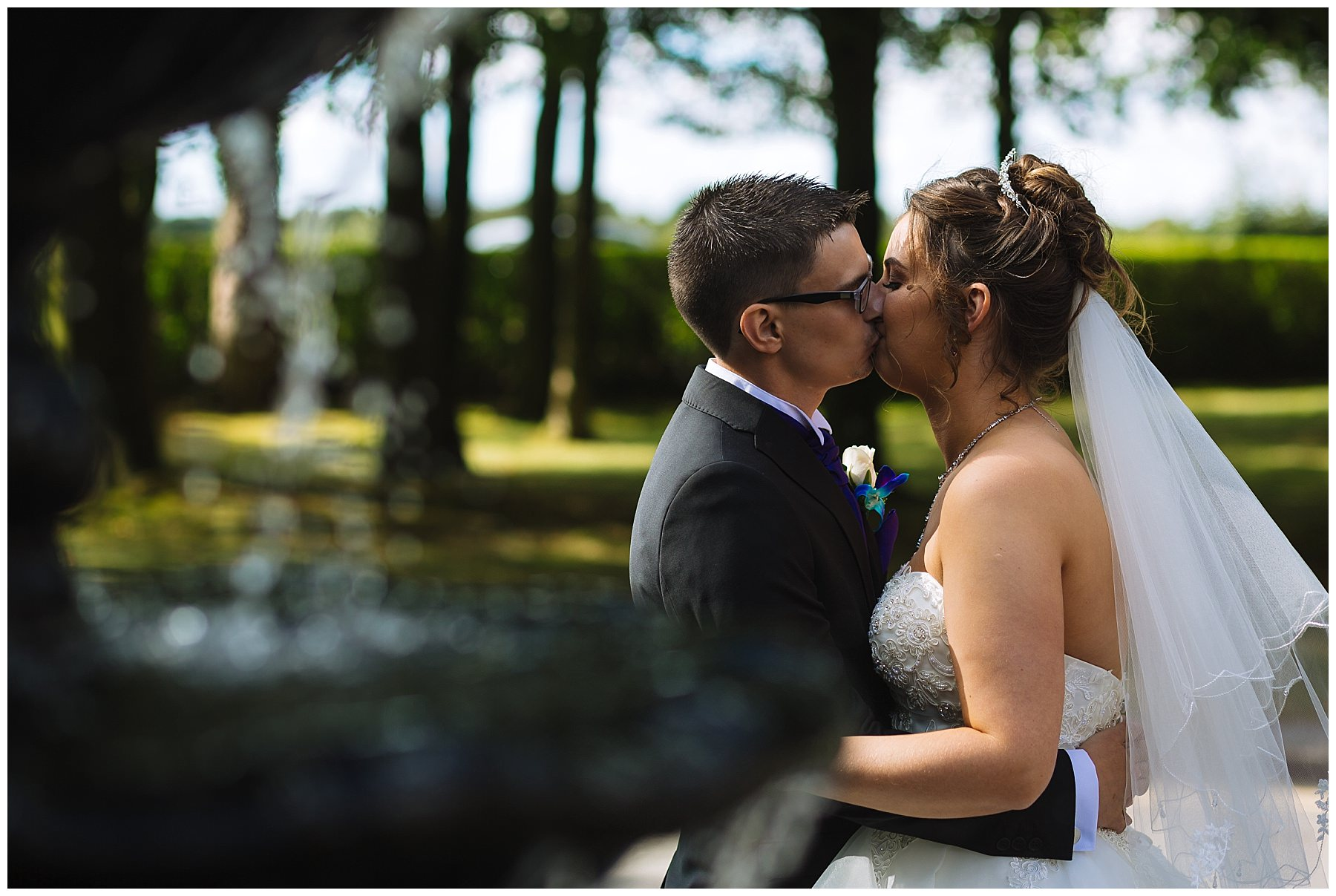 wedding couple kiss in front of fountain at kilhey court