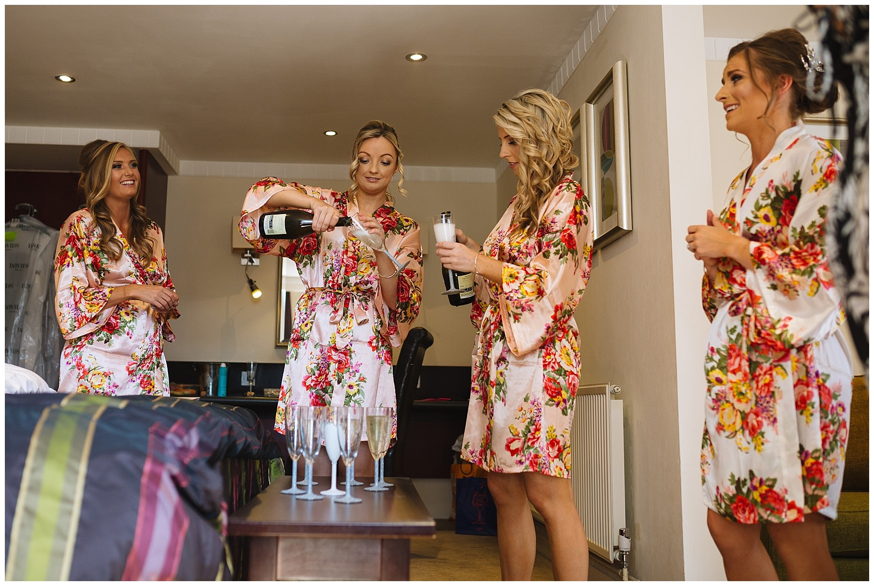 bridesmaids pour champagne during bridal prep