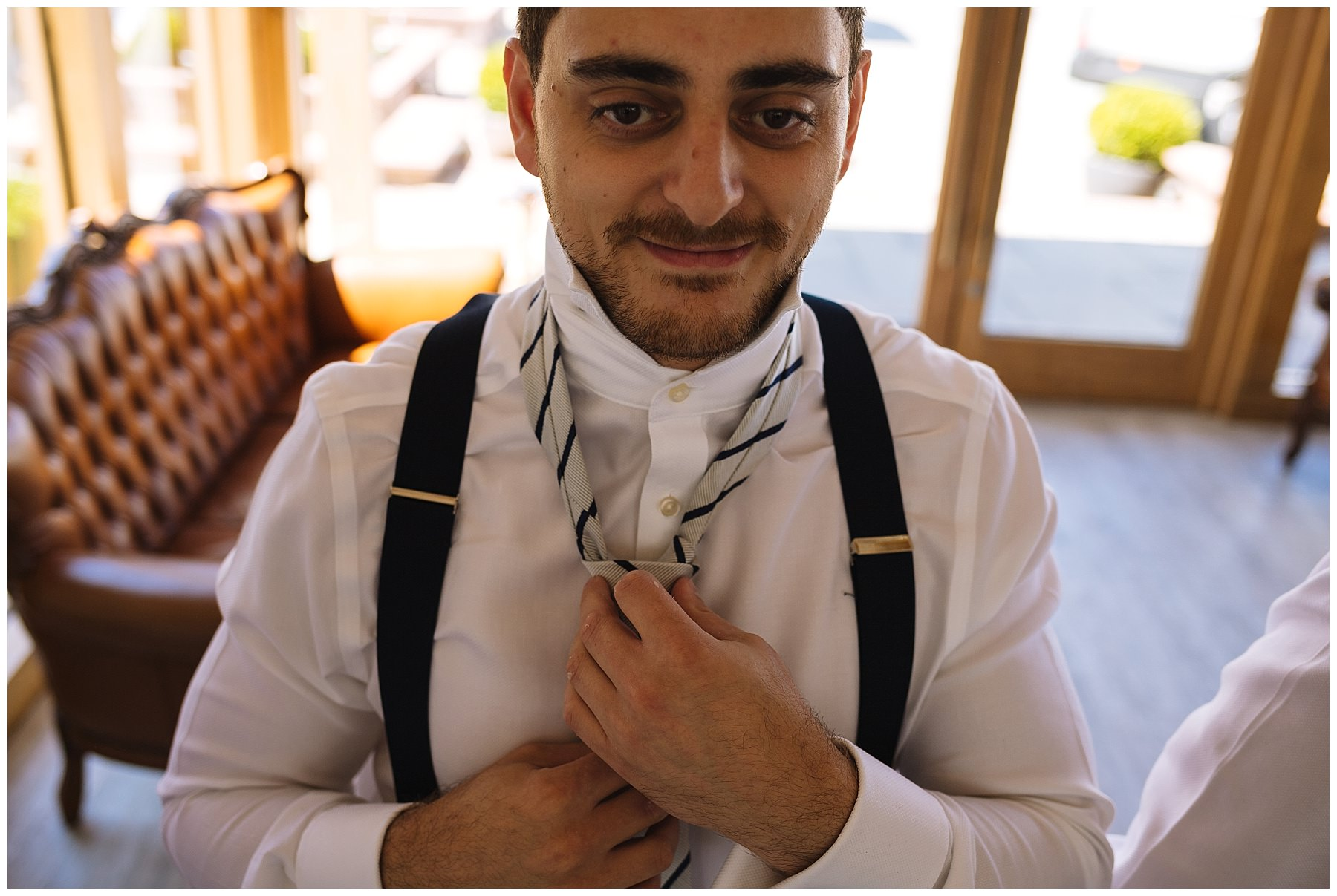 Groom puts on tie ahead of wedding