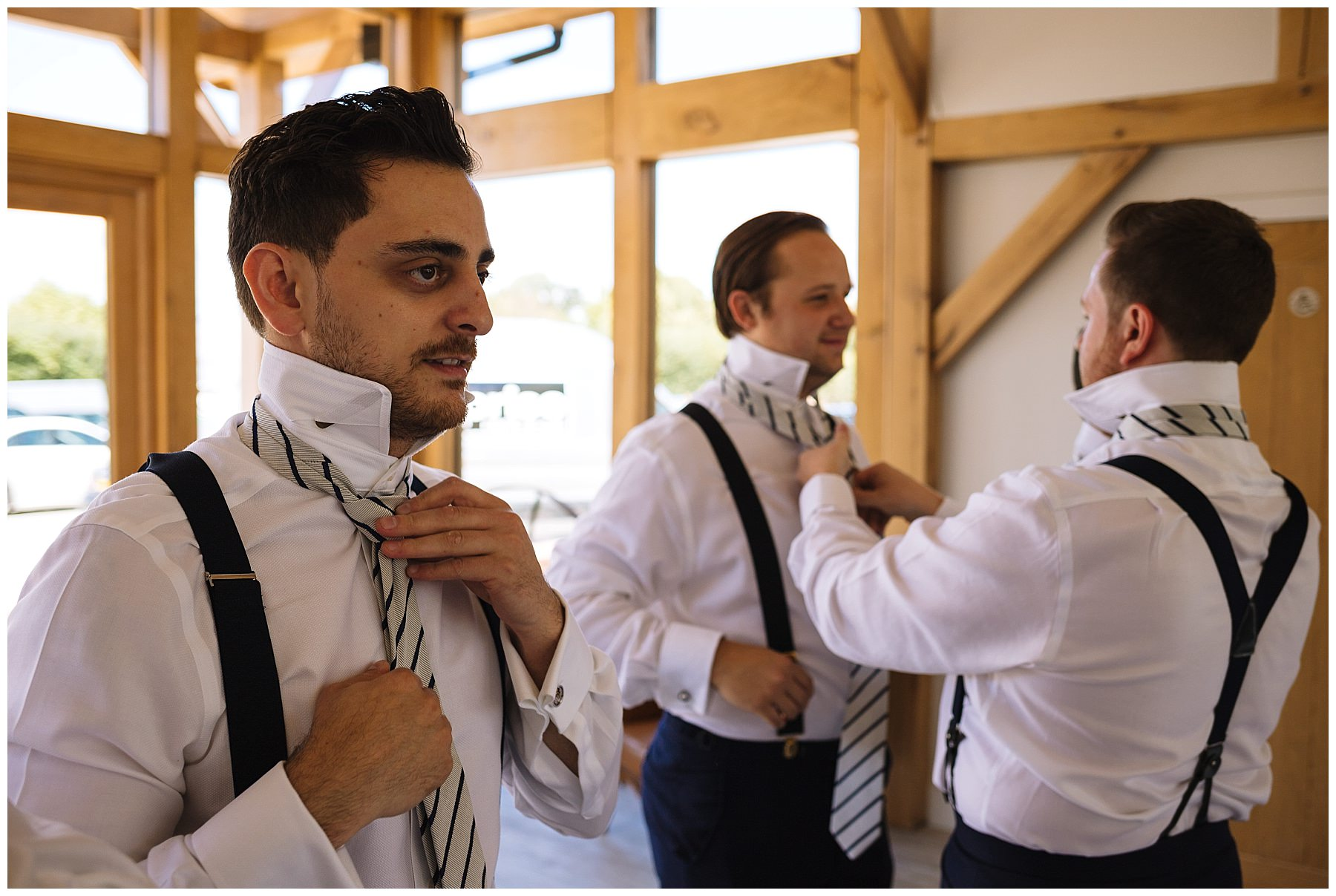 Groom and groomsmen fix their ties before wedding ceremony