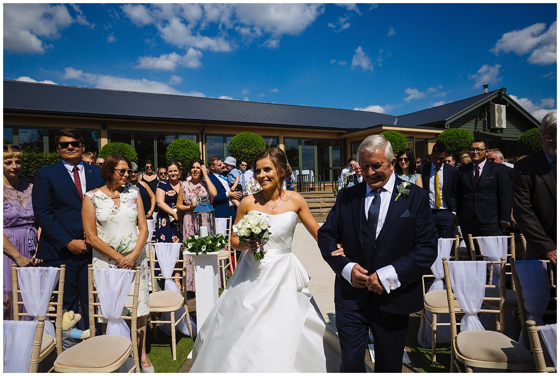 Bride is escorted by dad for outdoor summer ceremony
