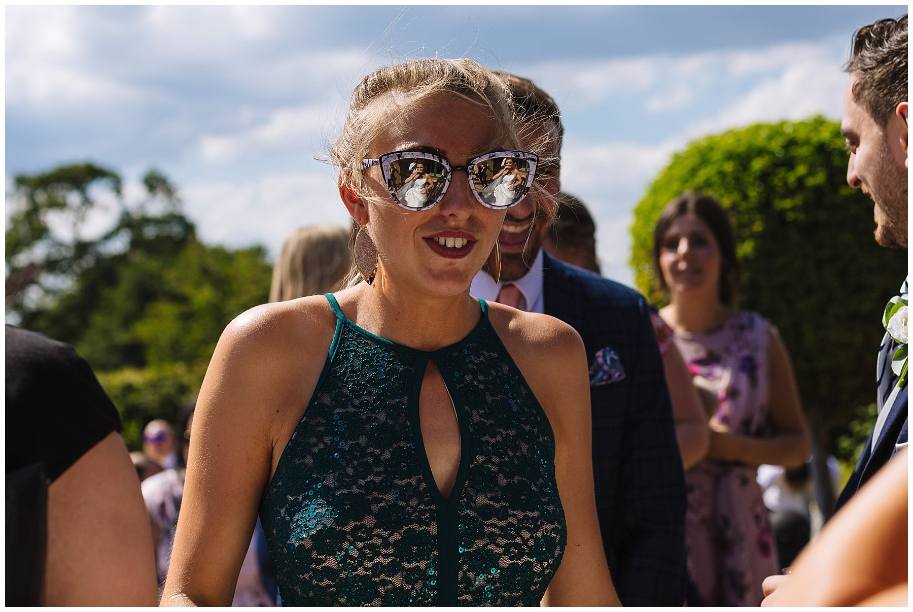 Bride reflected in guests sun glasses
