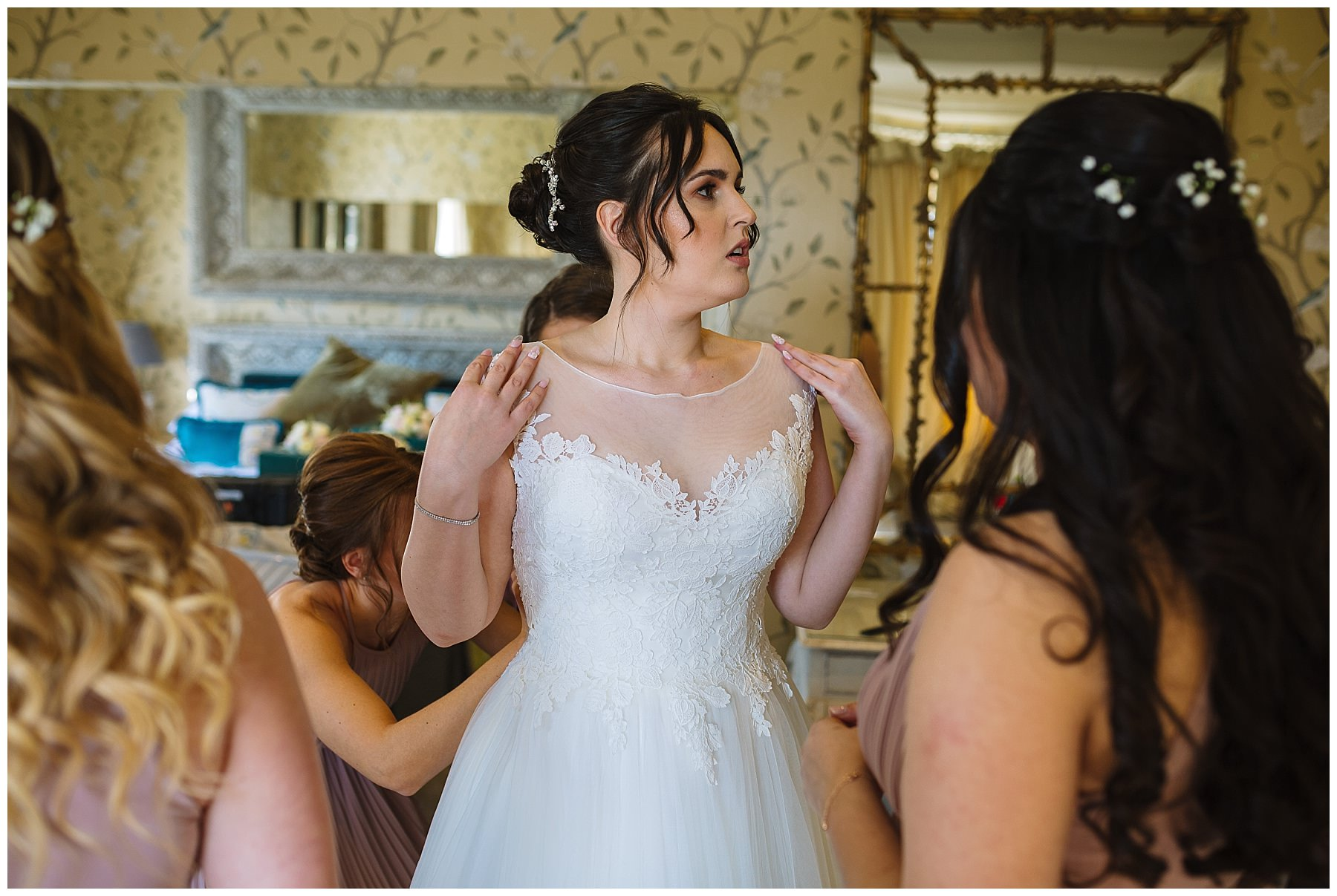 Bridesmaids help bride get into her dress