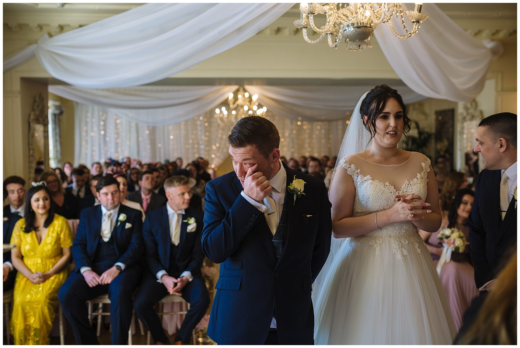 groom wipes away a tear during eaves hall wedding ceremony