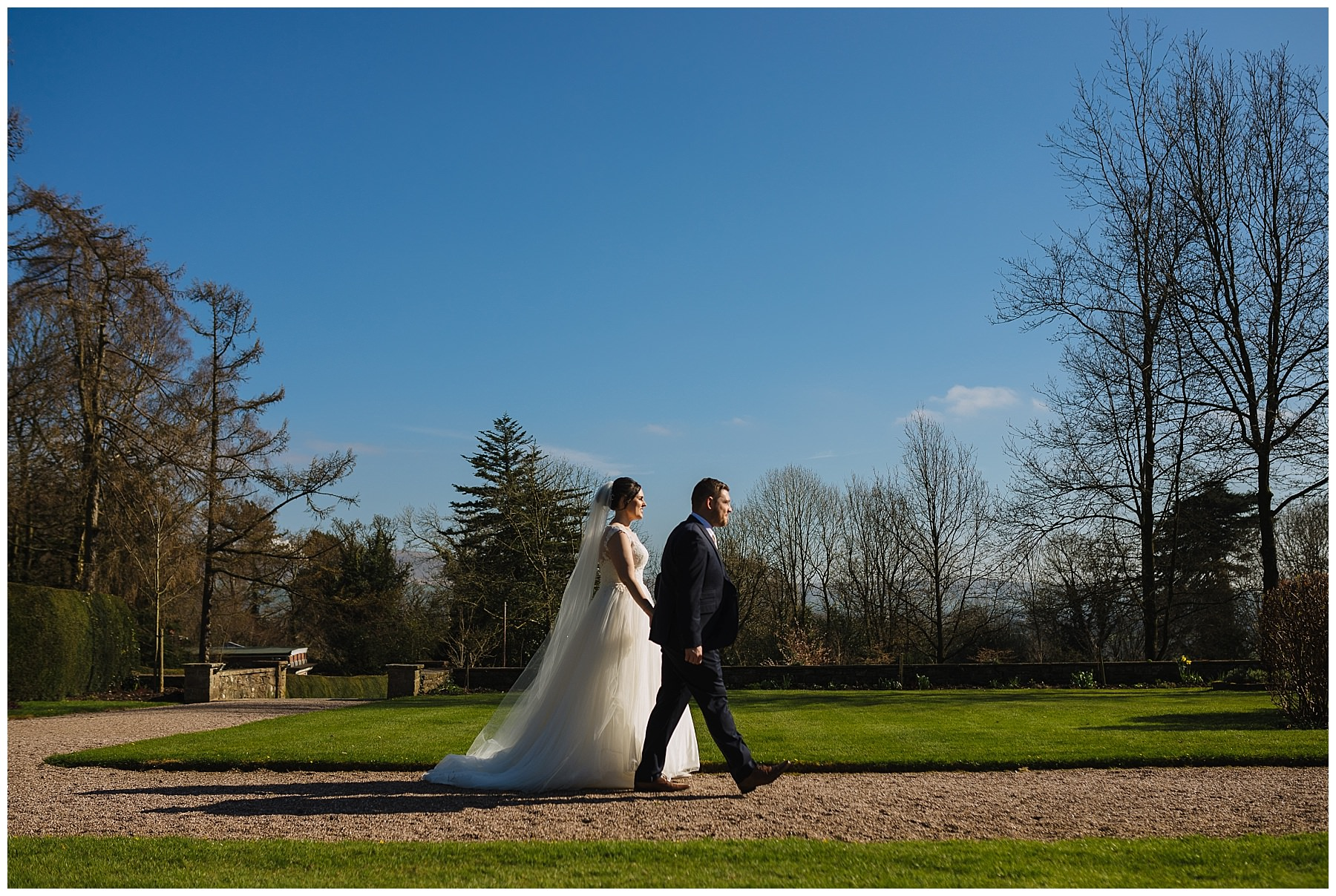 bride and groom walk through the gardens at eaves hall
