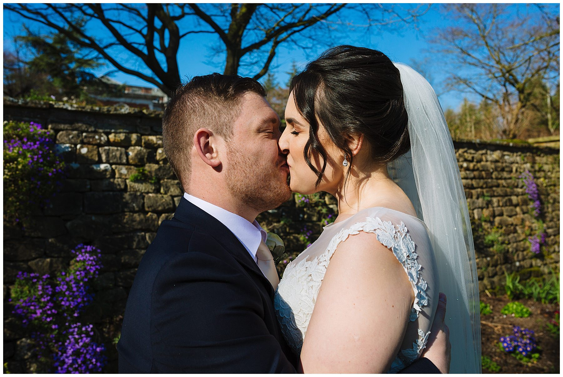 bride and groom kiss in the gardens at Eaves Hall