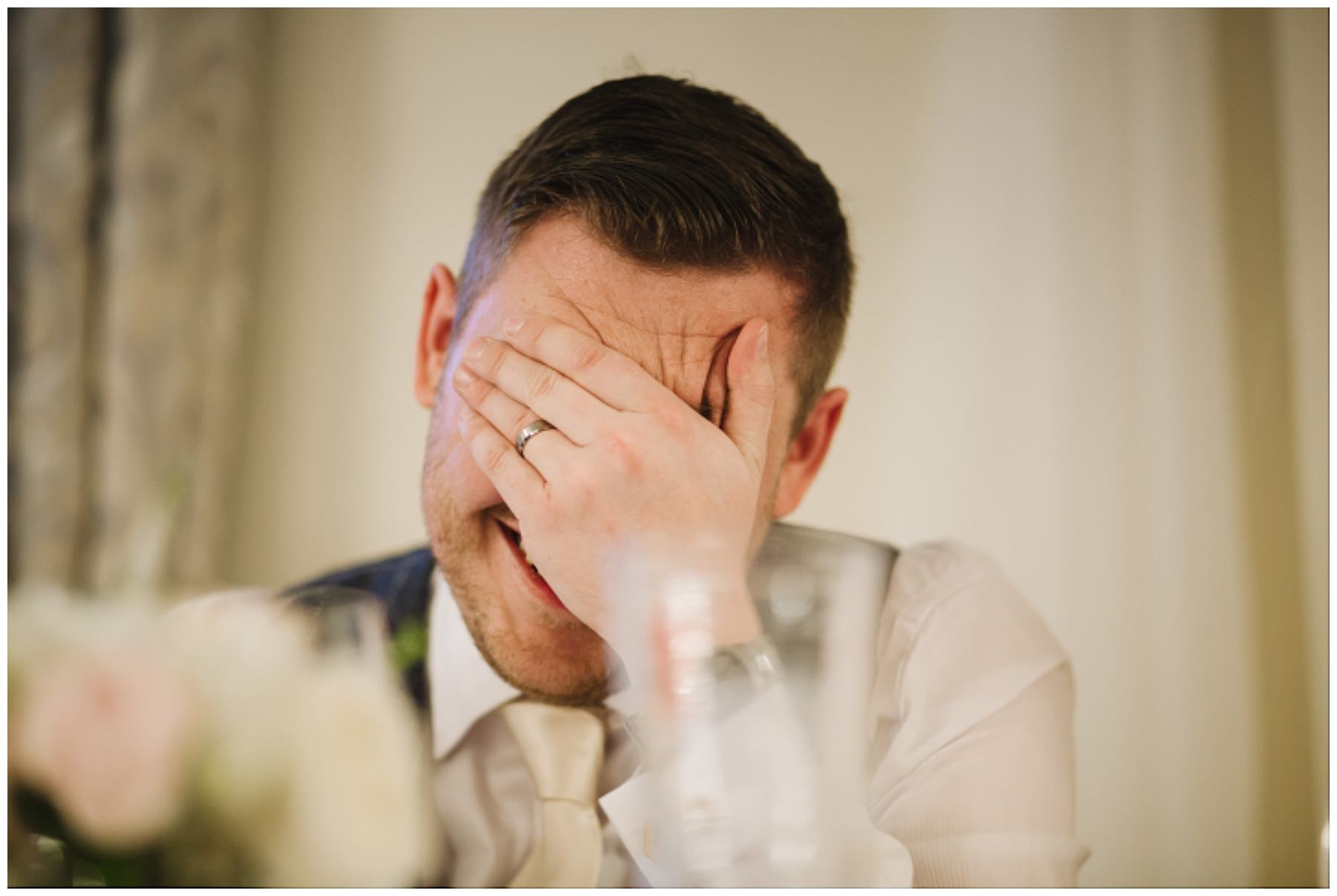 groom holds his head in his hands inn reaction to best mans speech
