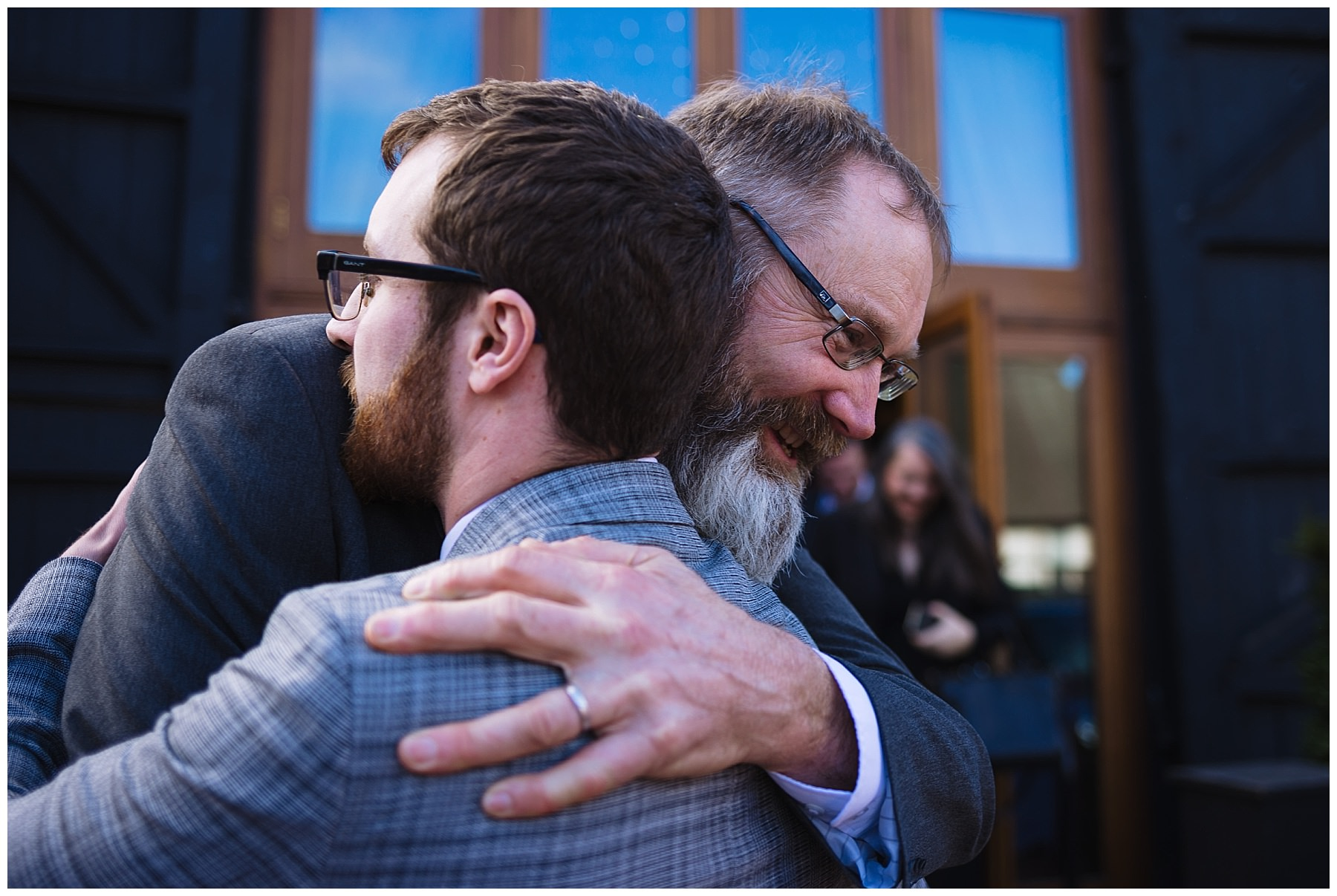 Father of the bride hugs groom after wedding ceremony