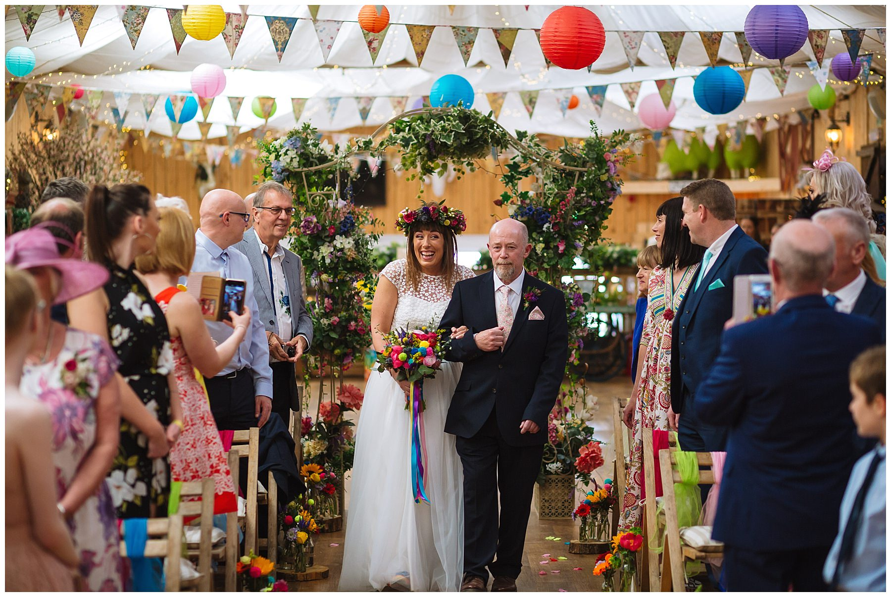 bride walks down the isle at the wellbeing farm arm in arm with dad