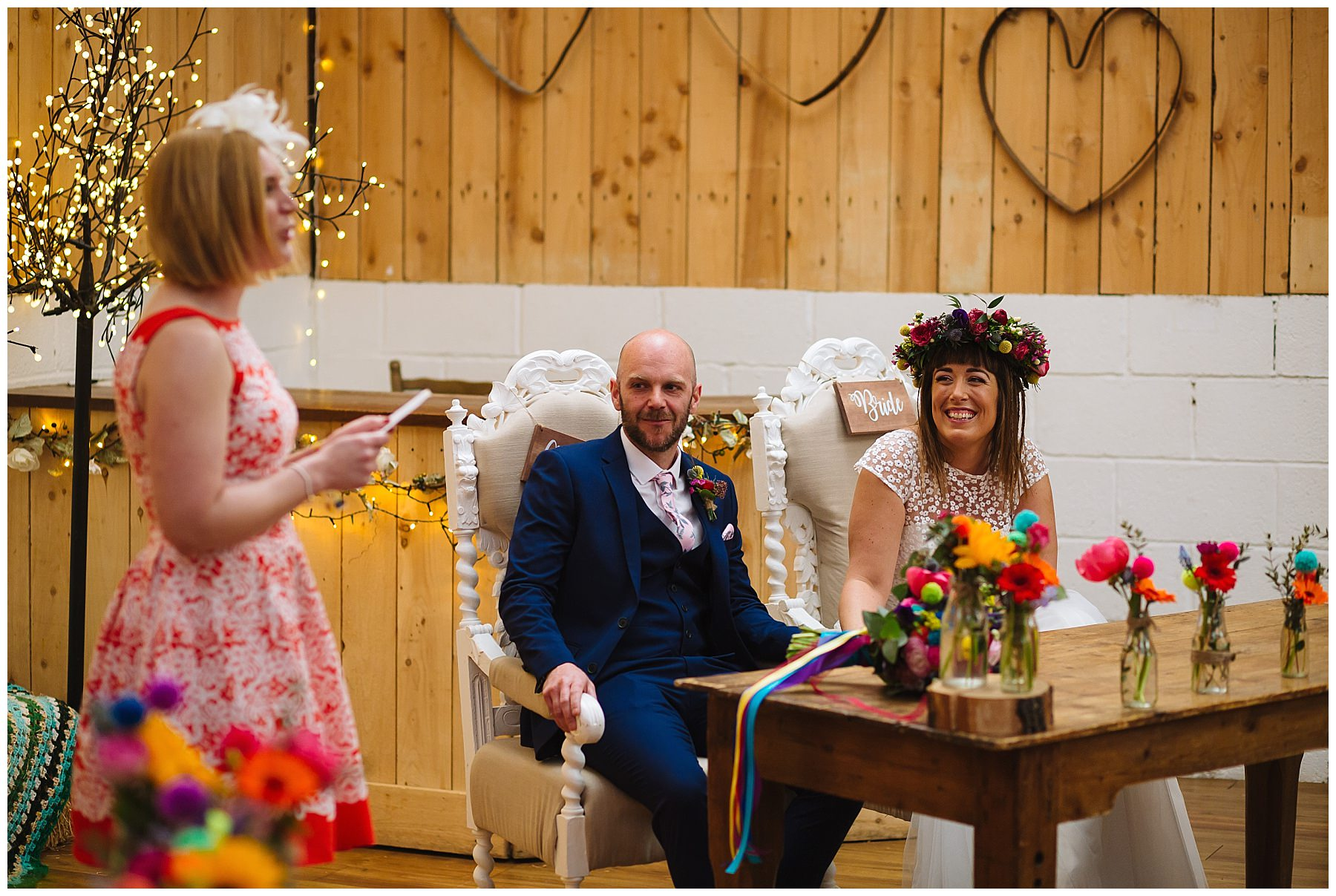 bride and groom look on as guest gives a reading during the wedding ceremony