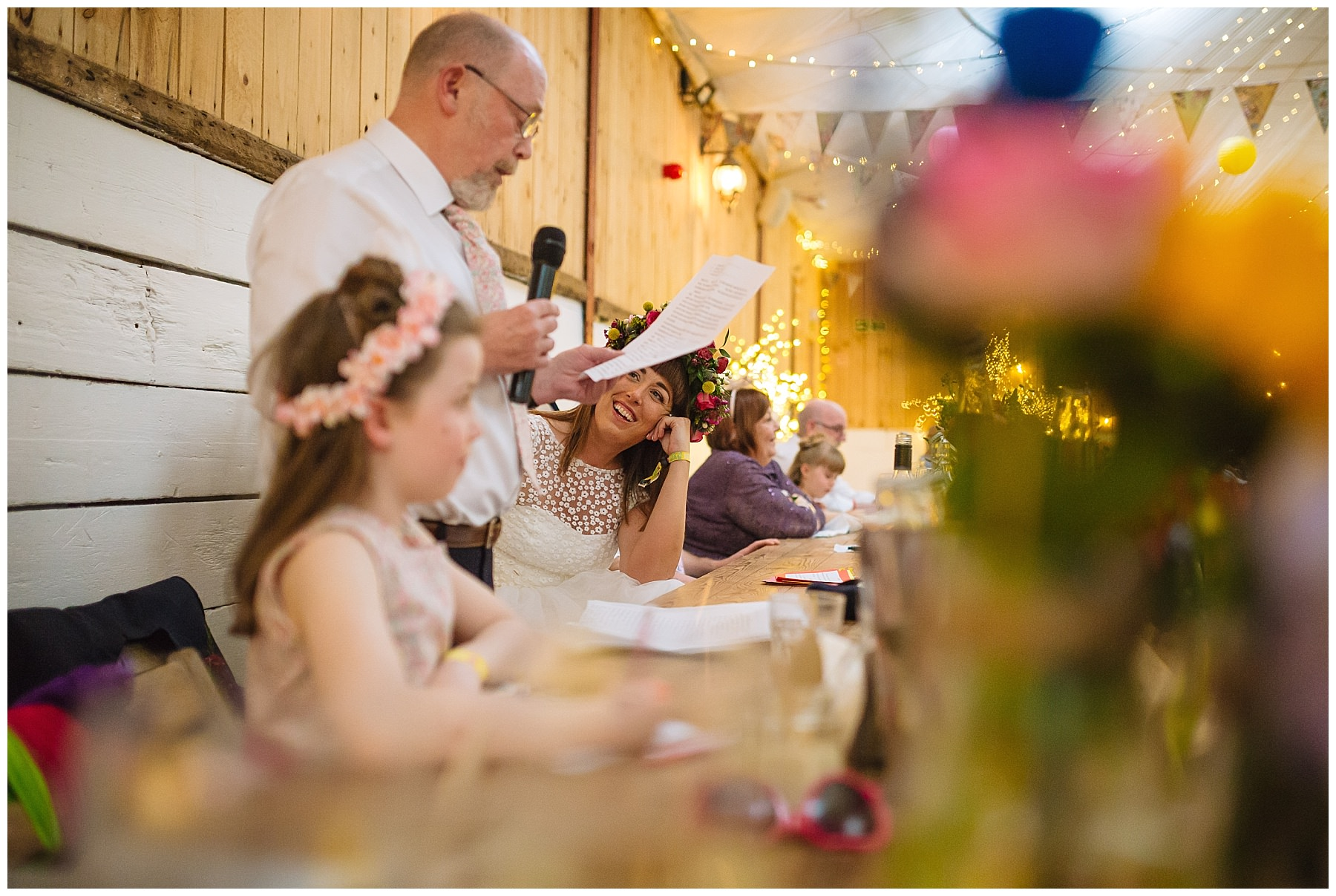 bride looks on as her dad gives speech