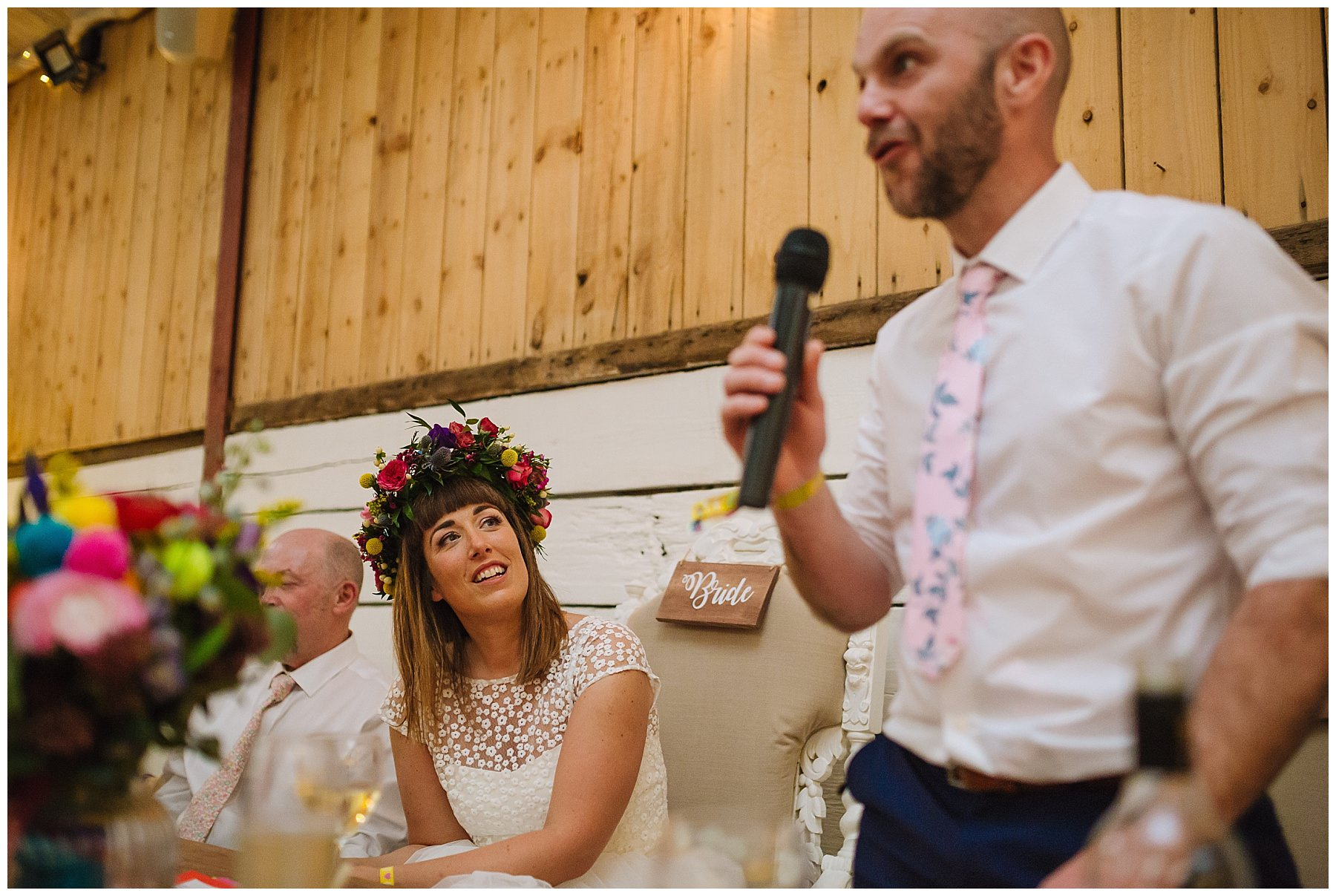 bride looks at her husband as he gives a speech at the wellbeing farm wedding